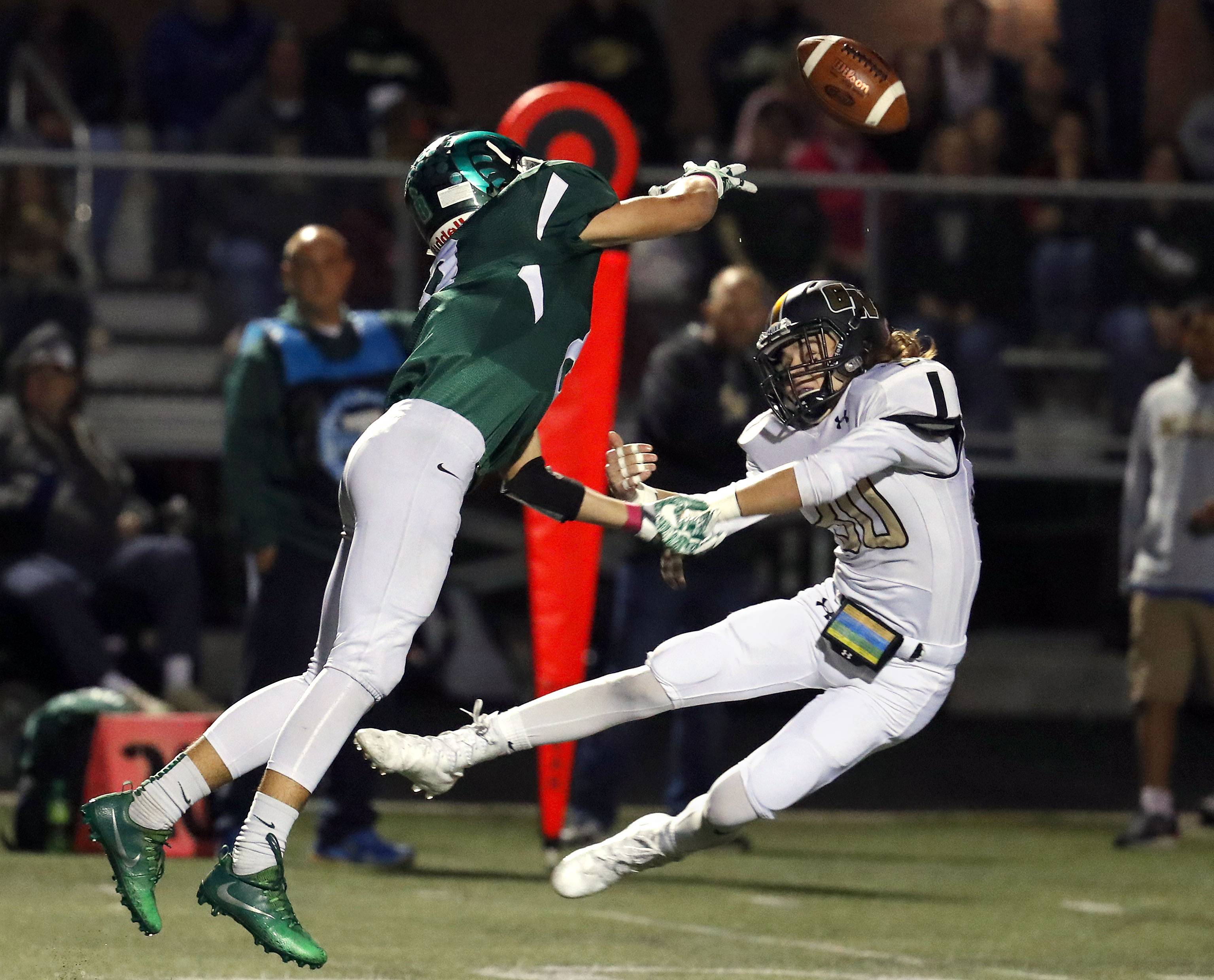 Grayslake Central's Peter Brewster, left, and Grayslake North's Garrick McGregor go up for a pass Friday night at Grayslake Central.