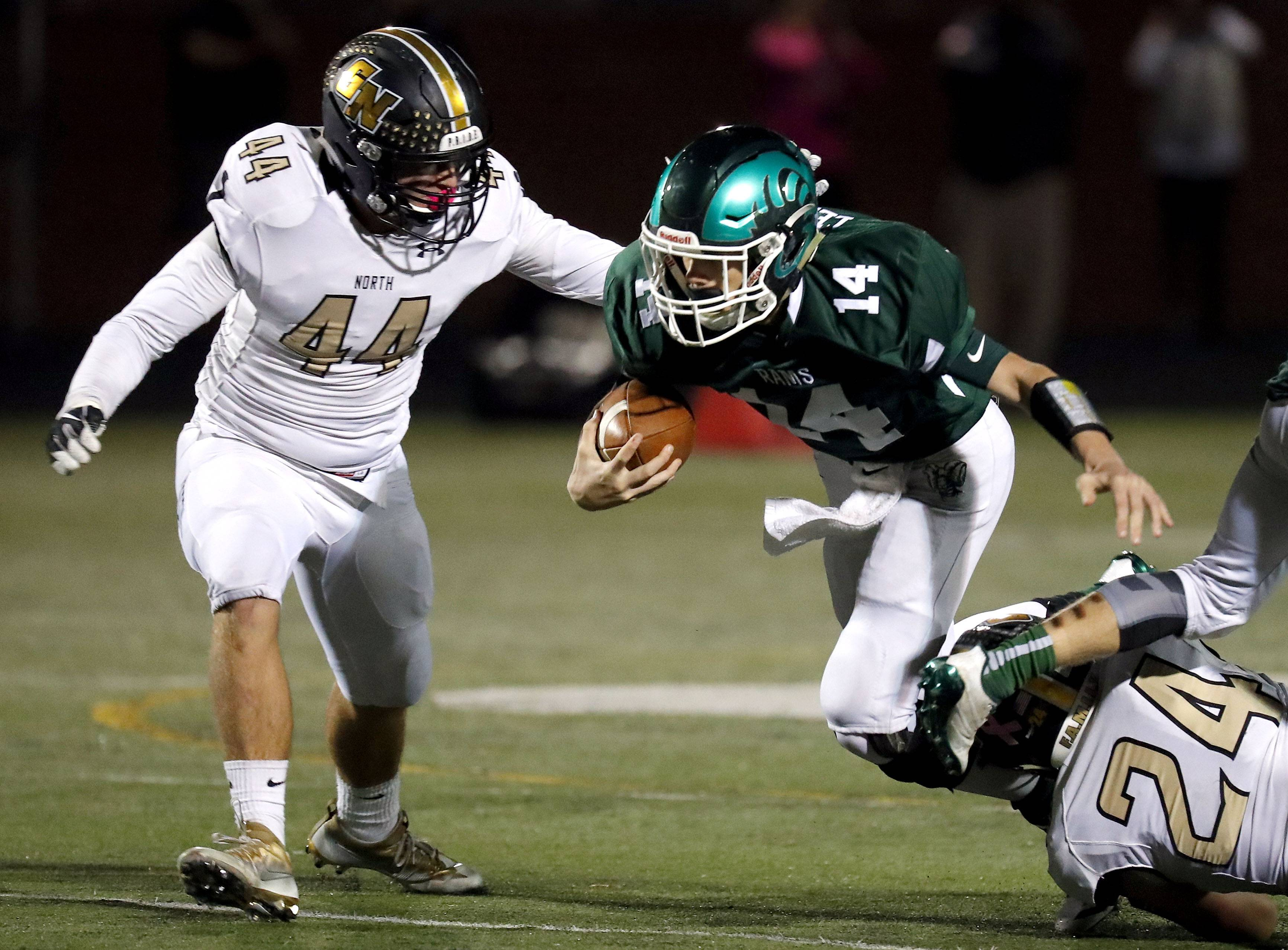 Grayslake Central's Sam Lennartz (14) tries to get away from Grayslake North's Adam George (44) and Michael Jordan on Friday night at Grayslake Central.
