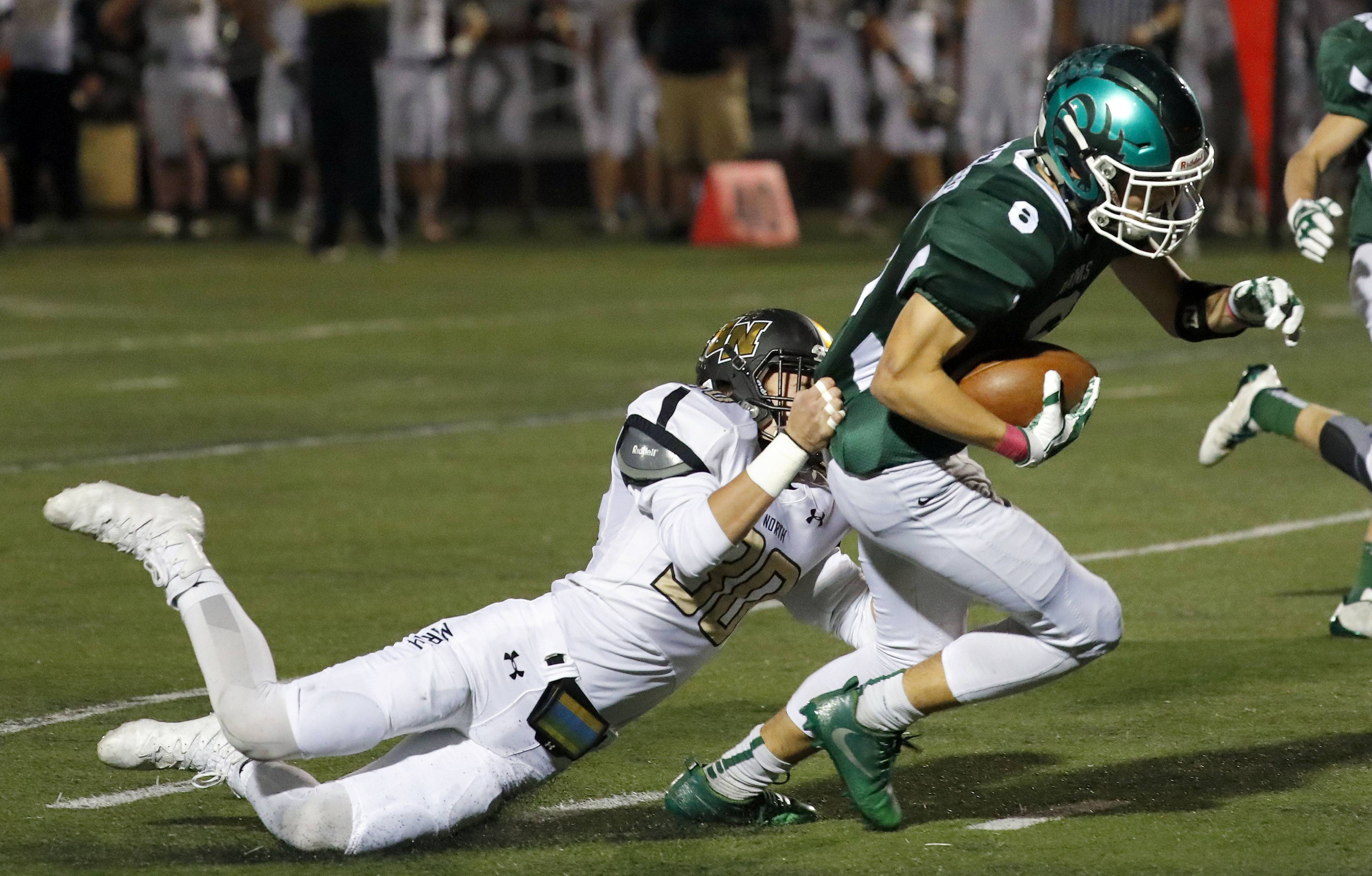 Grayslake Central's Peter Brewster, right, drags Grayslake North's Garrick McGregor after a catch Friday night at Grayslake Central.