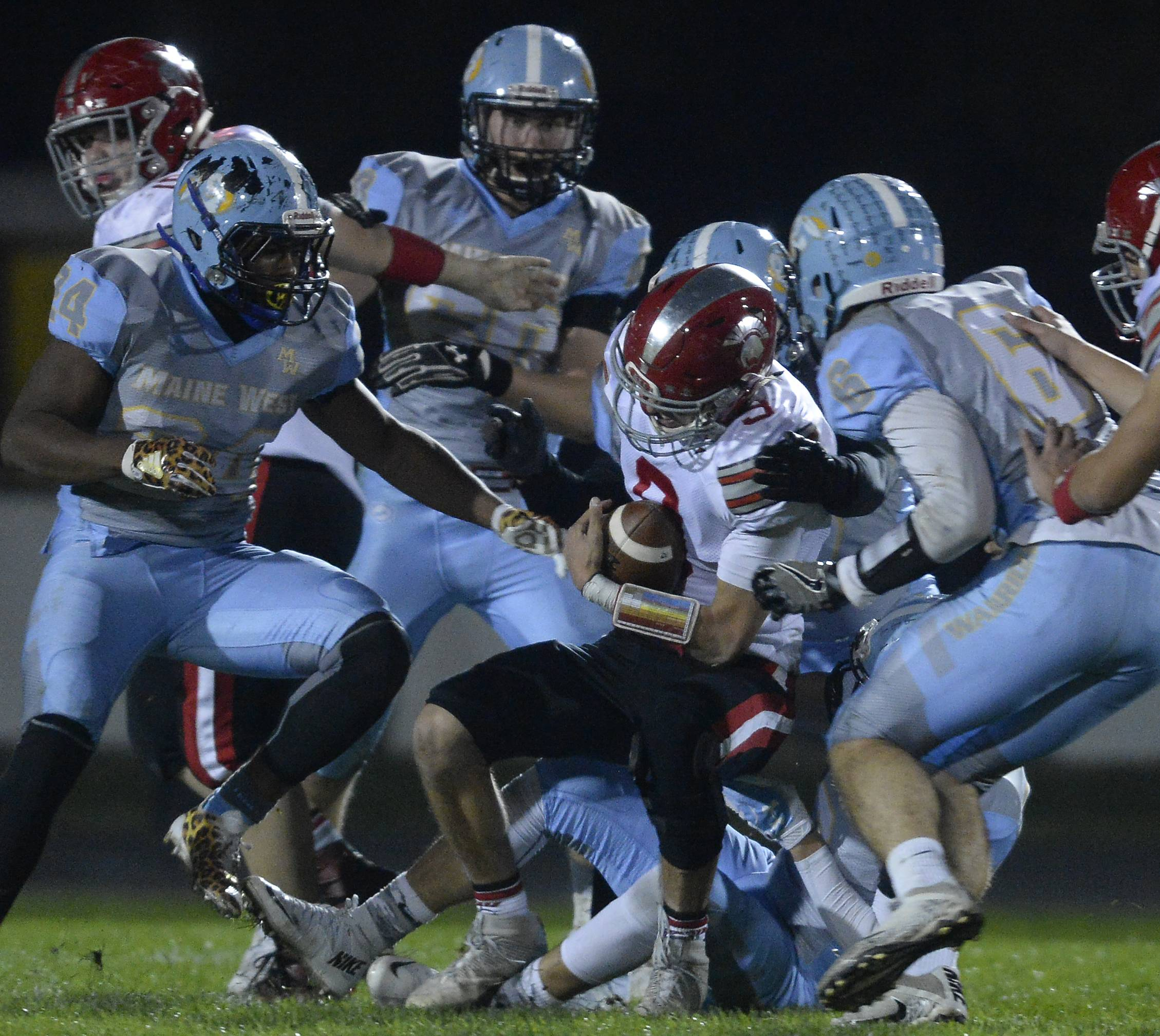 Maine West's defense brings down Deerfield quarterback Jonah Silverglade in the first half Friday at Maine West.