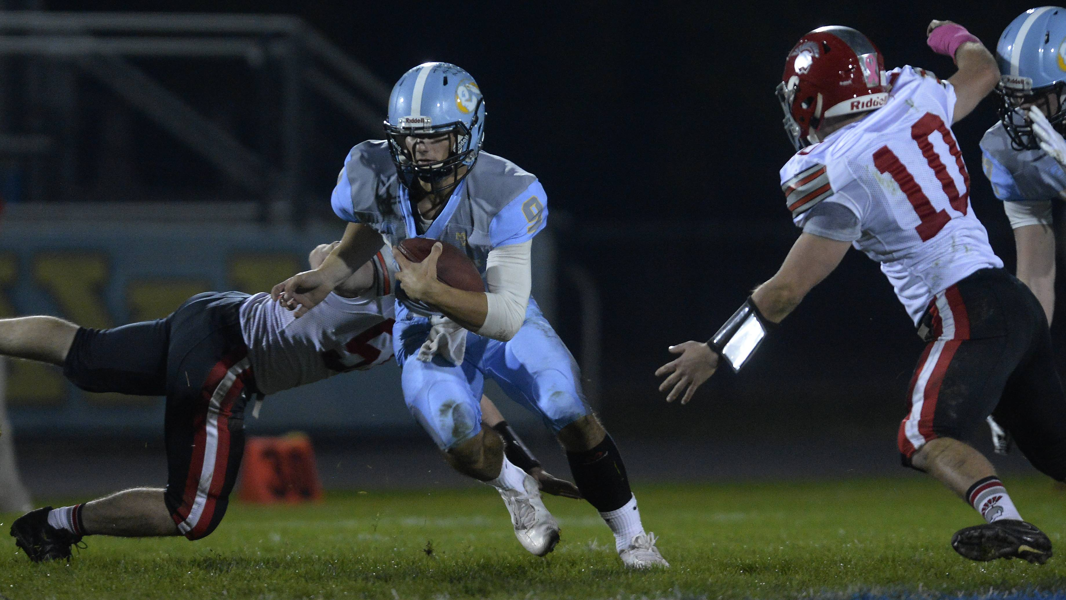 Maine West quarterback George Markakis keeps the ball for a first down in the second quarter against Deerfield on Friday.