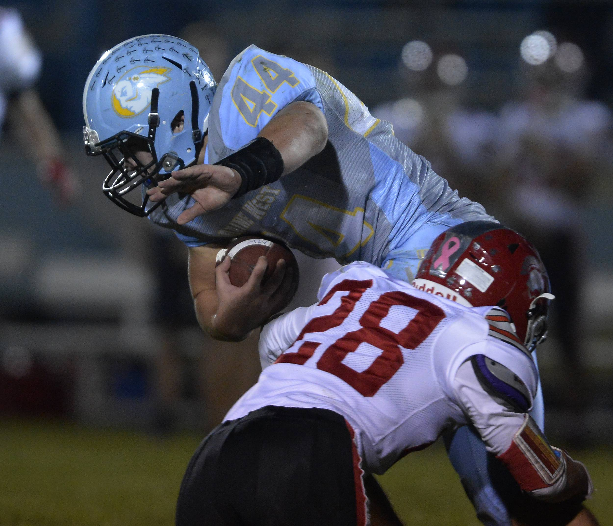 Maine West's Jake Bellizzi battles Deerfield's Adam Pottinger for yardage in the first half Friday at Maine West.