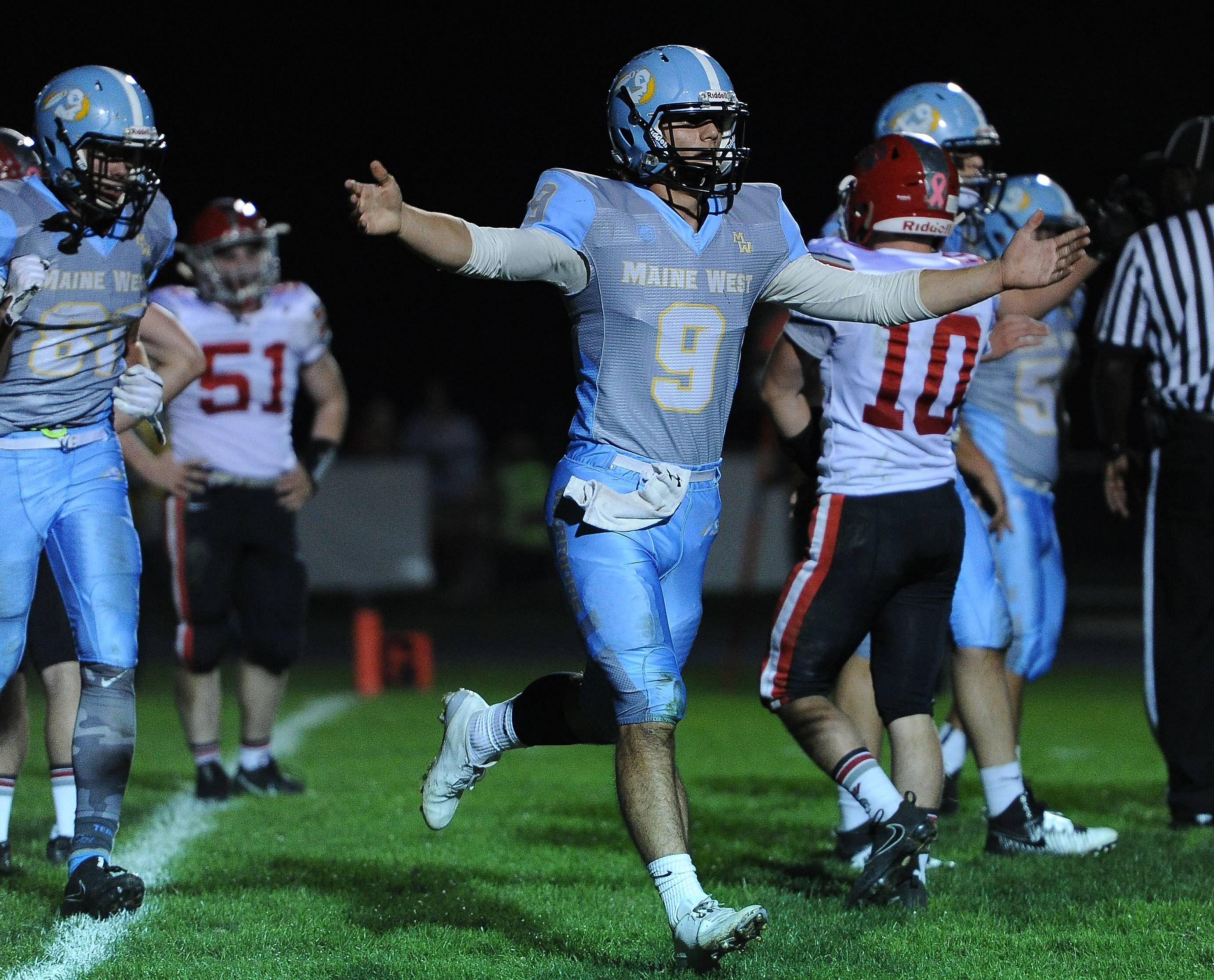 Maine West quarterback George Markakis keeps the ball for a TD and celebrates by running off the field on Friday against visiting Deerfield.