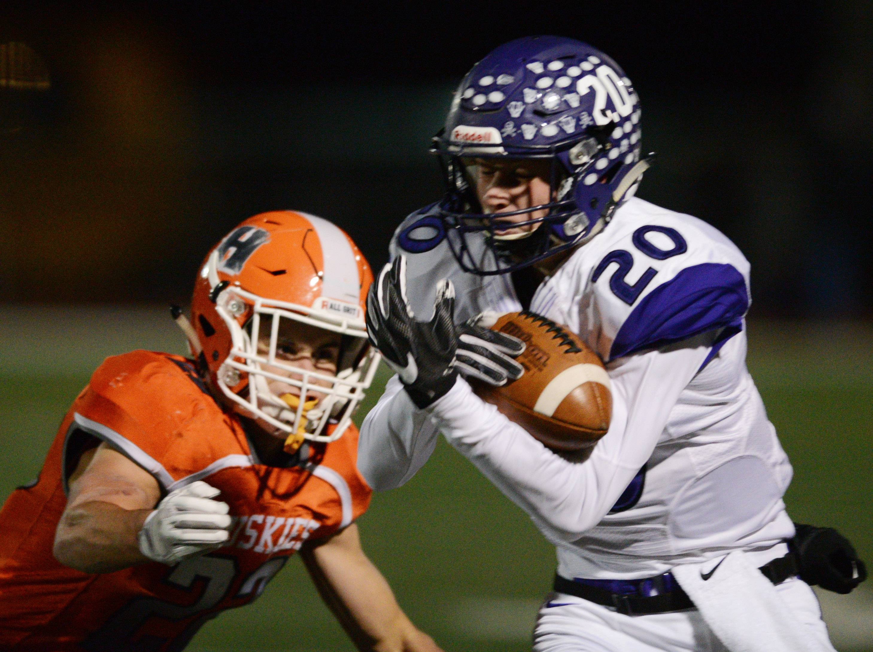 Rolling Meadows' Luke Nordman catches a pass in front of Hersey defender Luke Cecala first-round Class 7A playoff action in Arlington Heights on Friday.