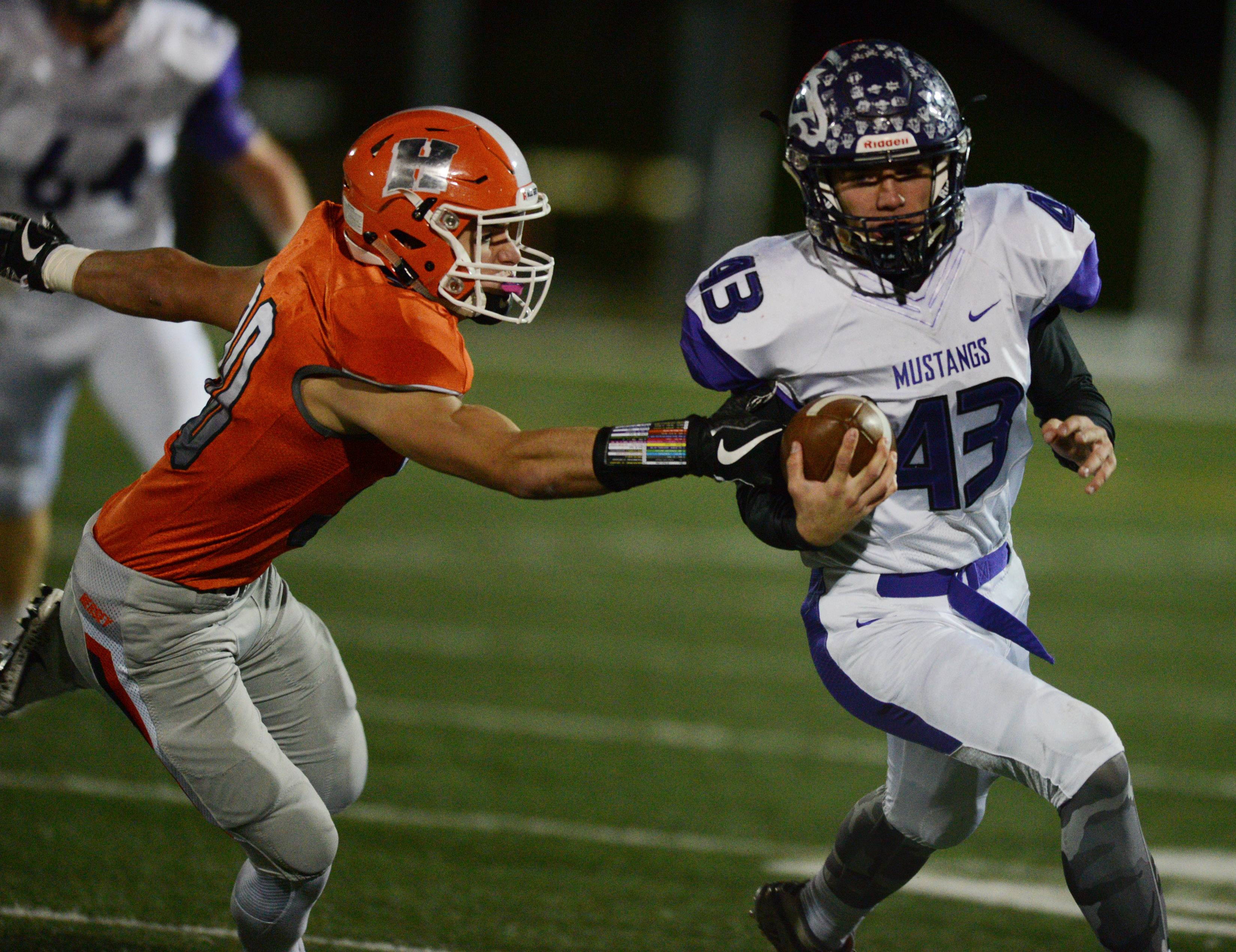 Rolling Meadows ball-carrier Tim Szylak gets past Hersey's Luke Picchiotti in Class 7A first-round playoff action in Arlington Heights on Friday.