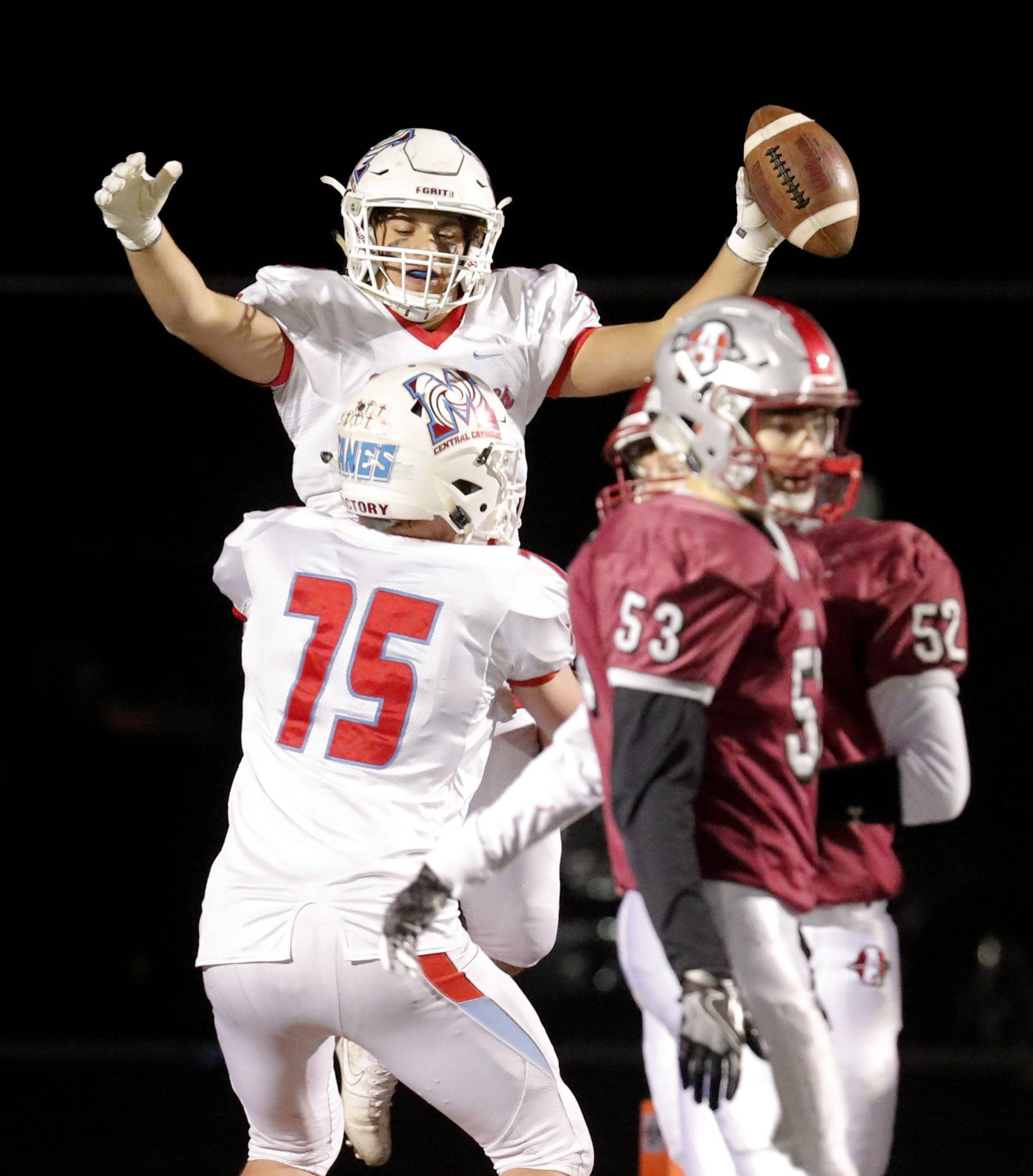 Marian Central's Pasquale Ricciardi celebrates with Kevin Herbst (75) after his TD catch during Class 5A first-round playoff action Friday in Antioch.
