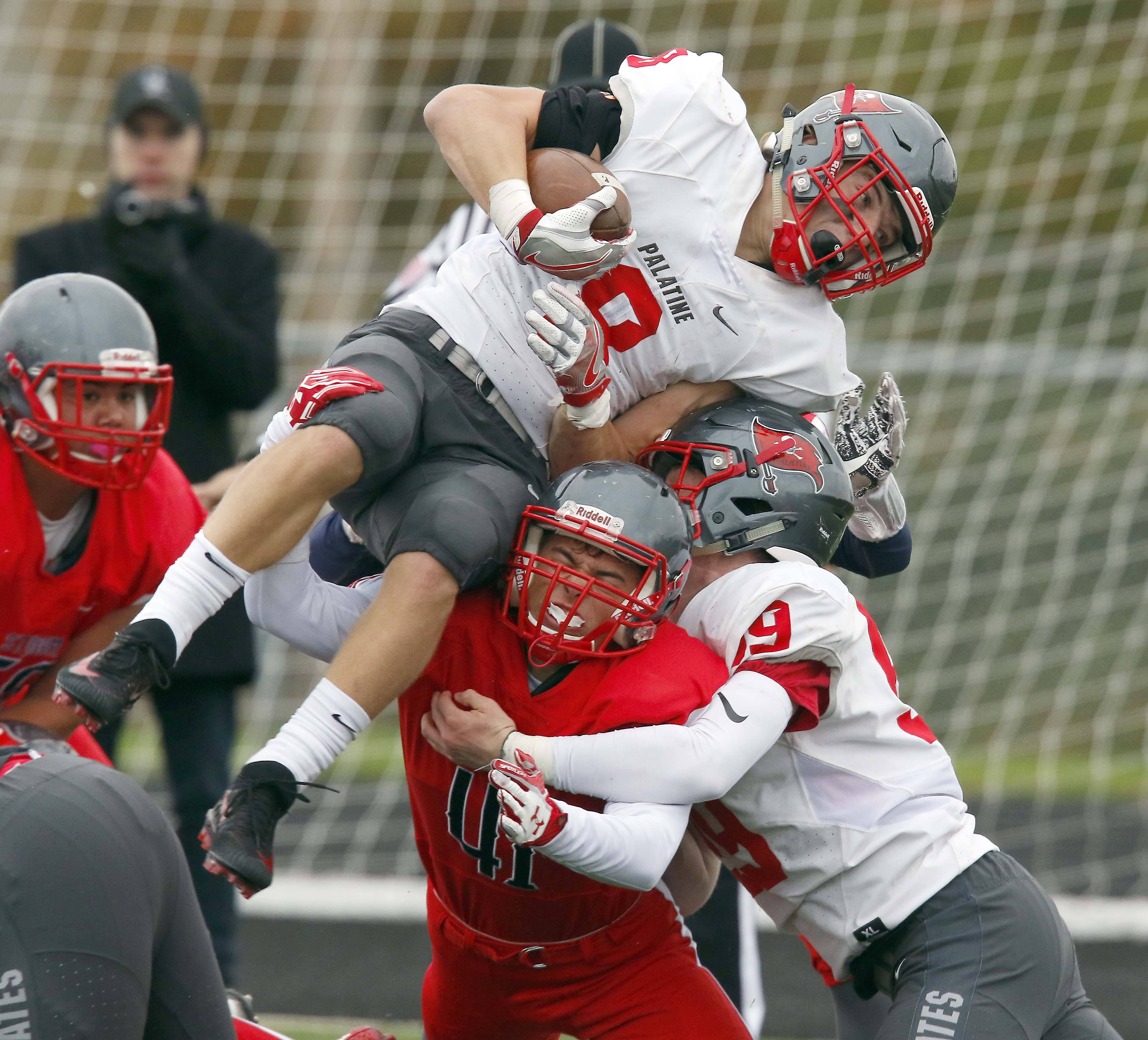 Palatine's Jake Moertl (8) goes up and over South Elgin's Patrick Noworol (41) Saturday during Palatine vs. South Elgin Class 8A football playoffs at Millennium Field in Streamwood.