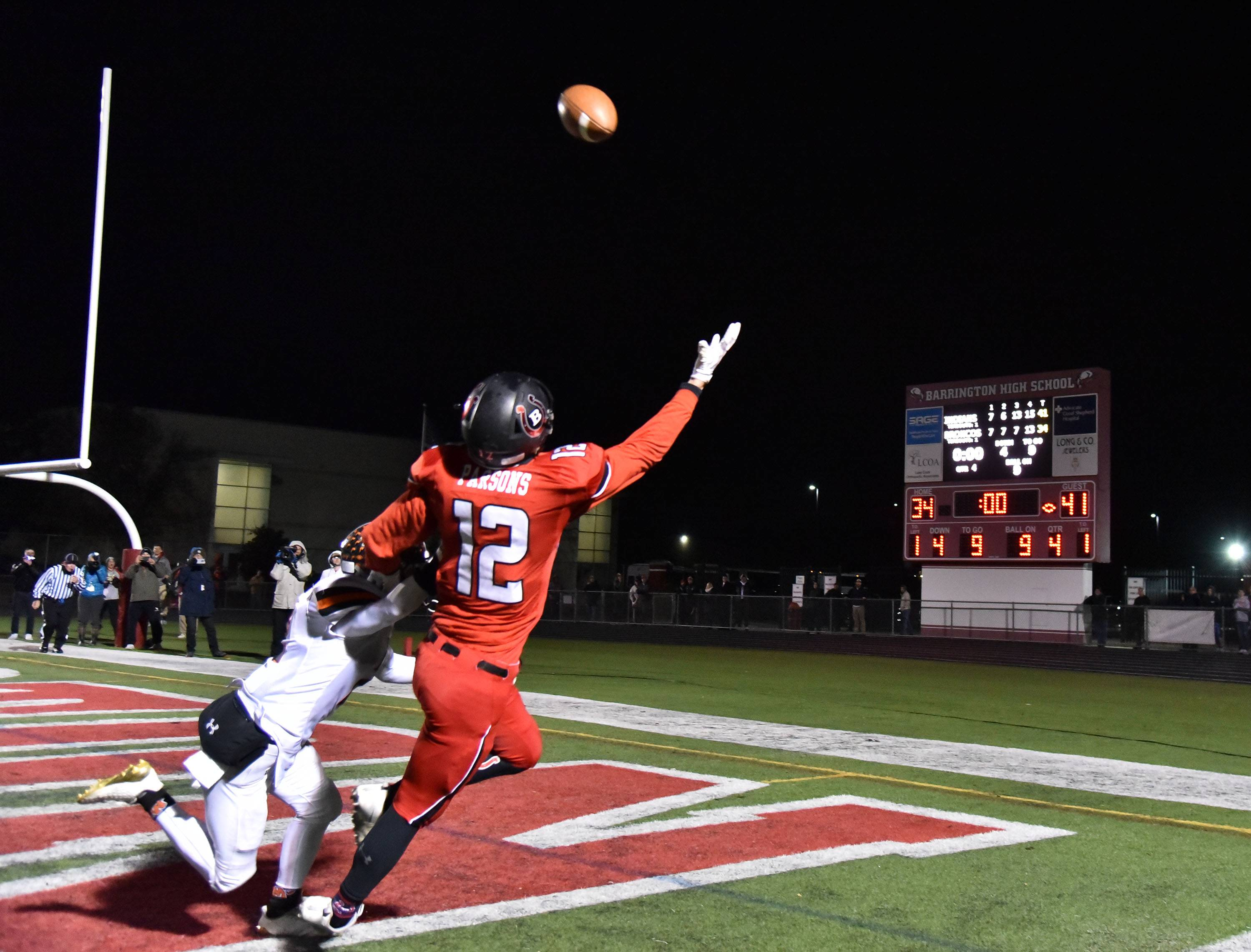 Down by a touchdown in overtime, Barrington's Jake Parsons reaches for a last-play pass in the end zone as Minooka's Colin Schuster defends Friday in the Class 8A football playoffs at Barrington Community Stadium.