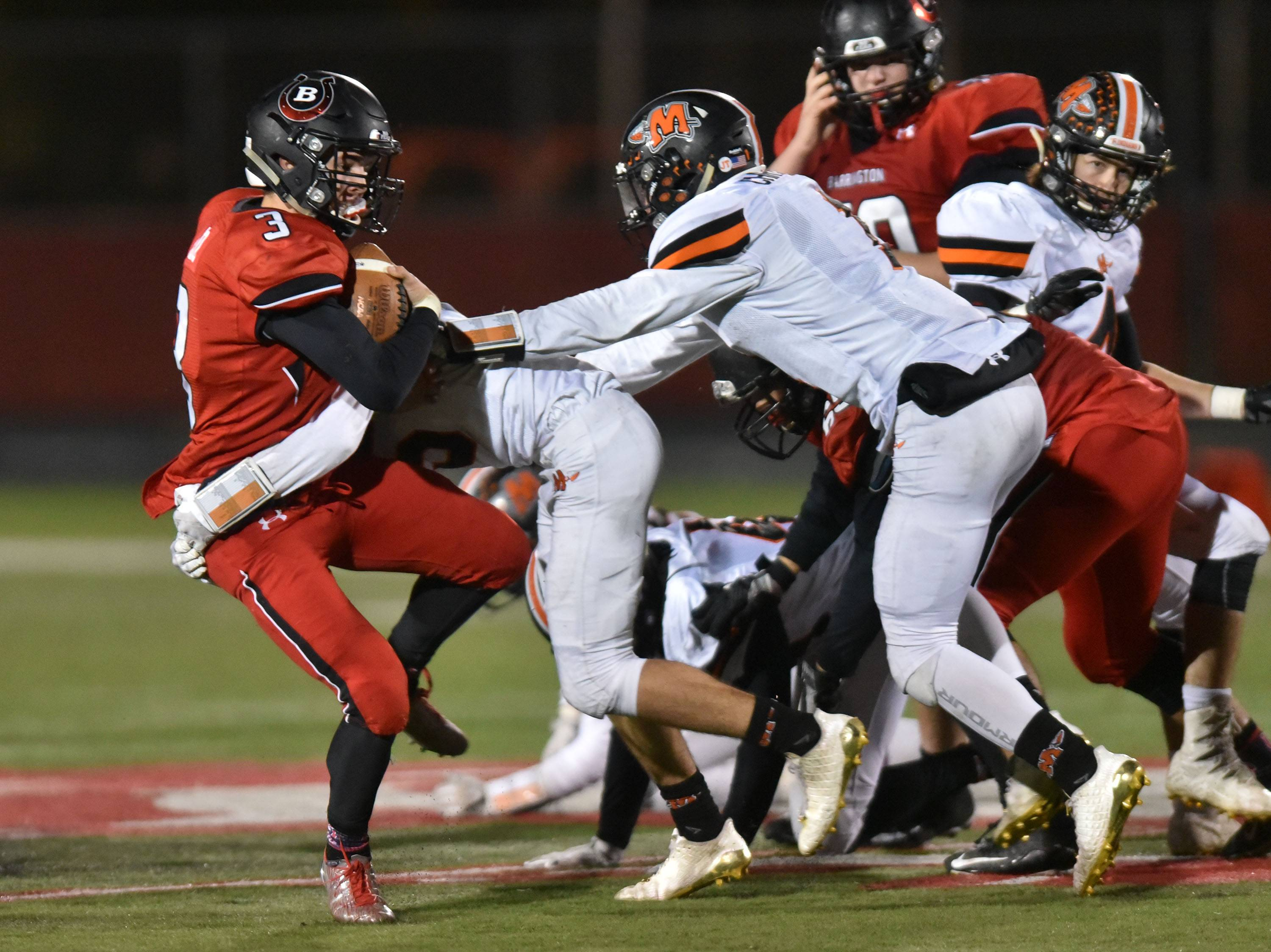 Barrington's Ray Niro is stopped by Minooka's Tyler Haase on Friday in the Class 8A playoffs at Barrington Community Stadium.