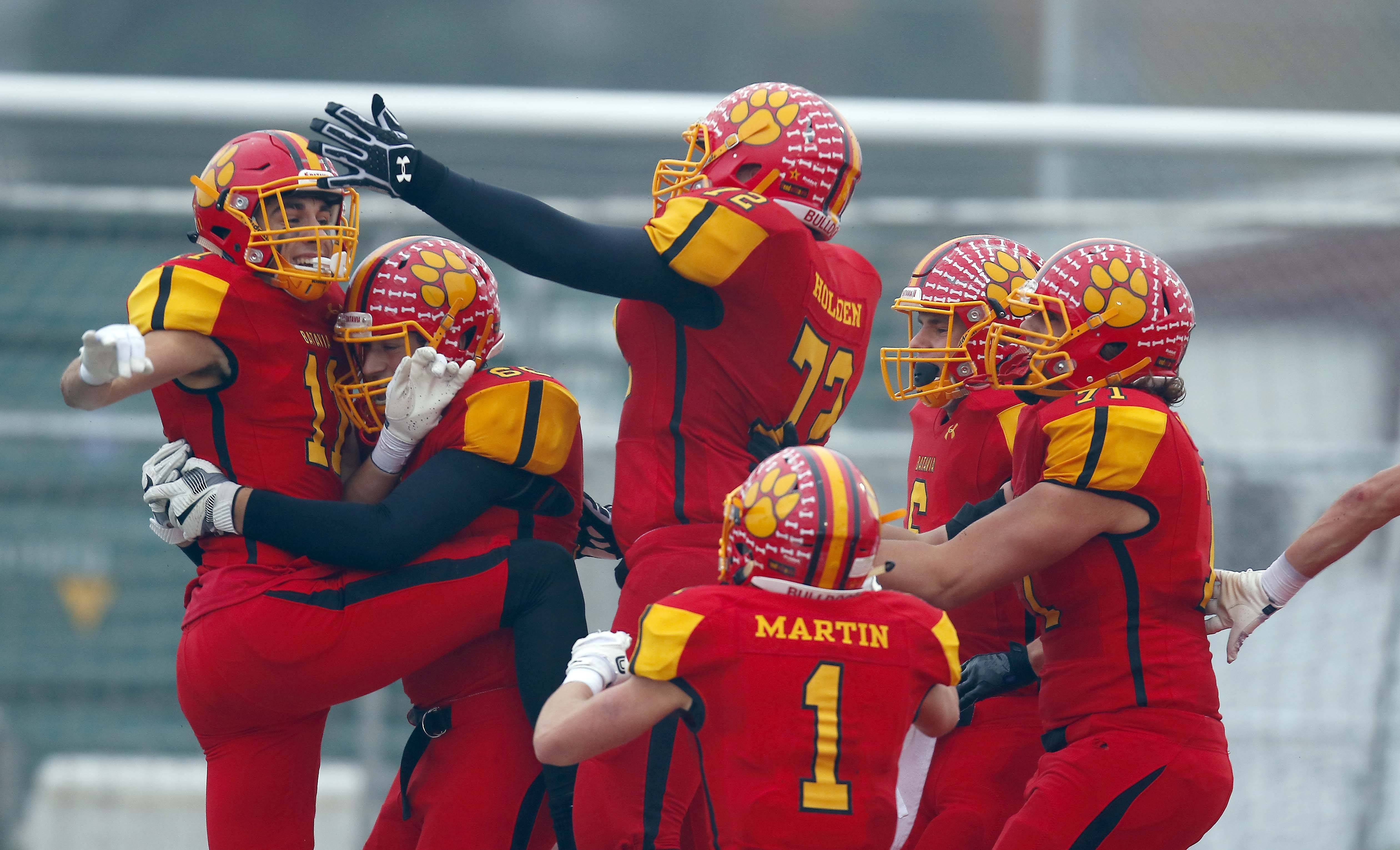 Batavia's Eric Peterson (11) is greeted by his teammates after catching a game-winning touchdown in overtime Saturday during the Class 7A football playoffs in Batavia.