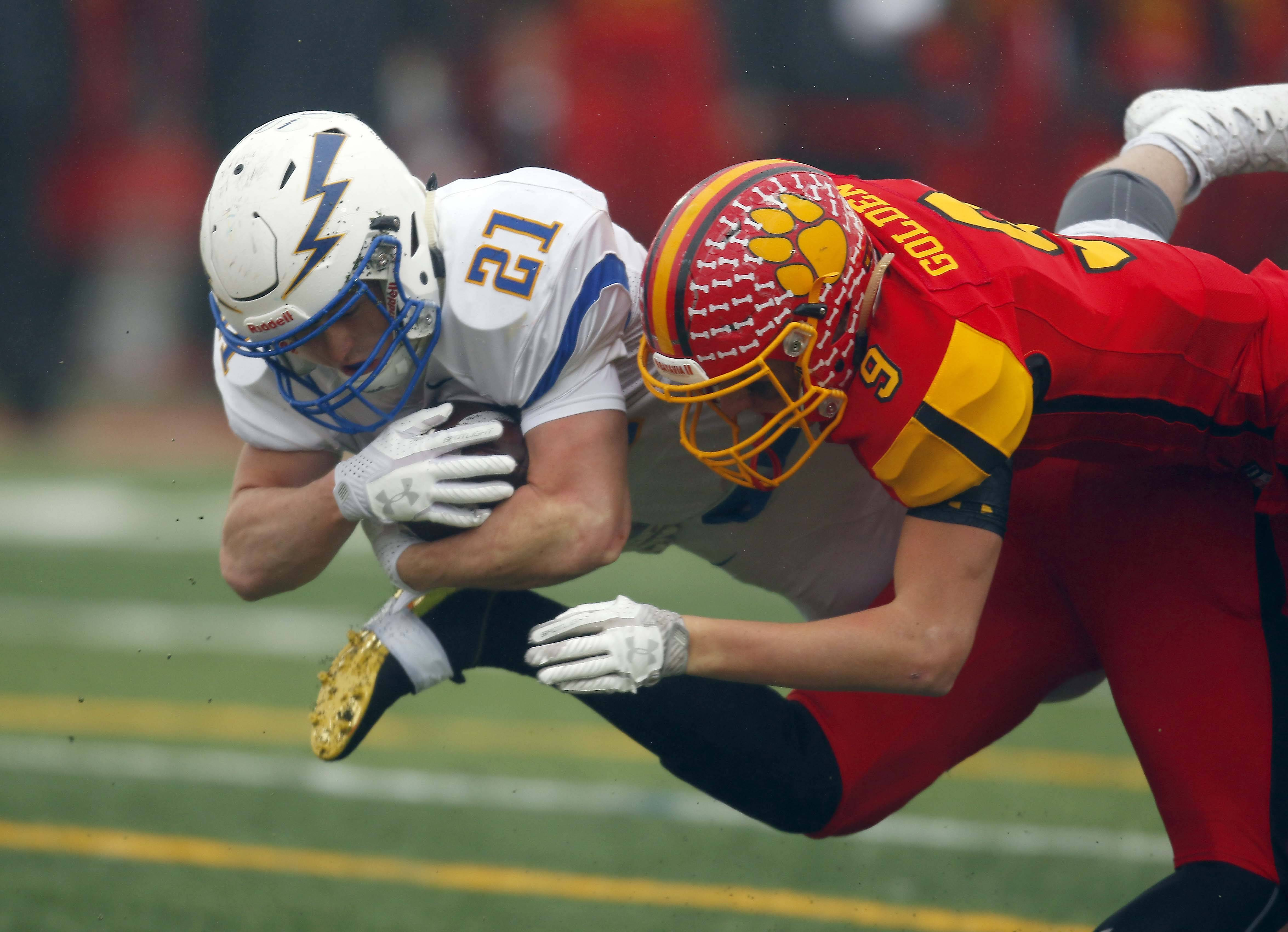 Wheaton North's Sam Singleton (21) and Batavia's John Golden (9) go airborne during a play Saturday during the IHSA Class 7A football playoffs in Batavia.