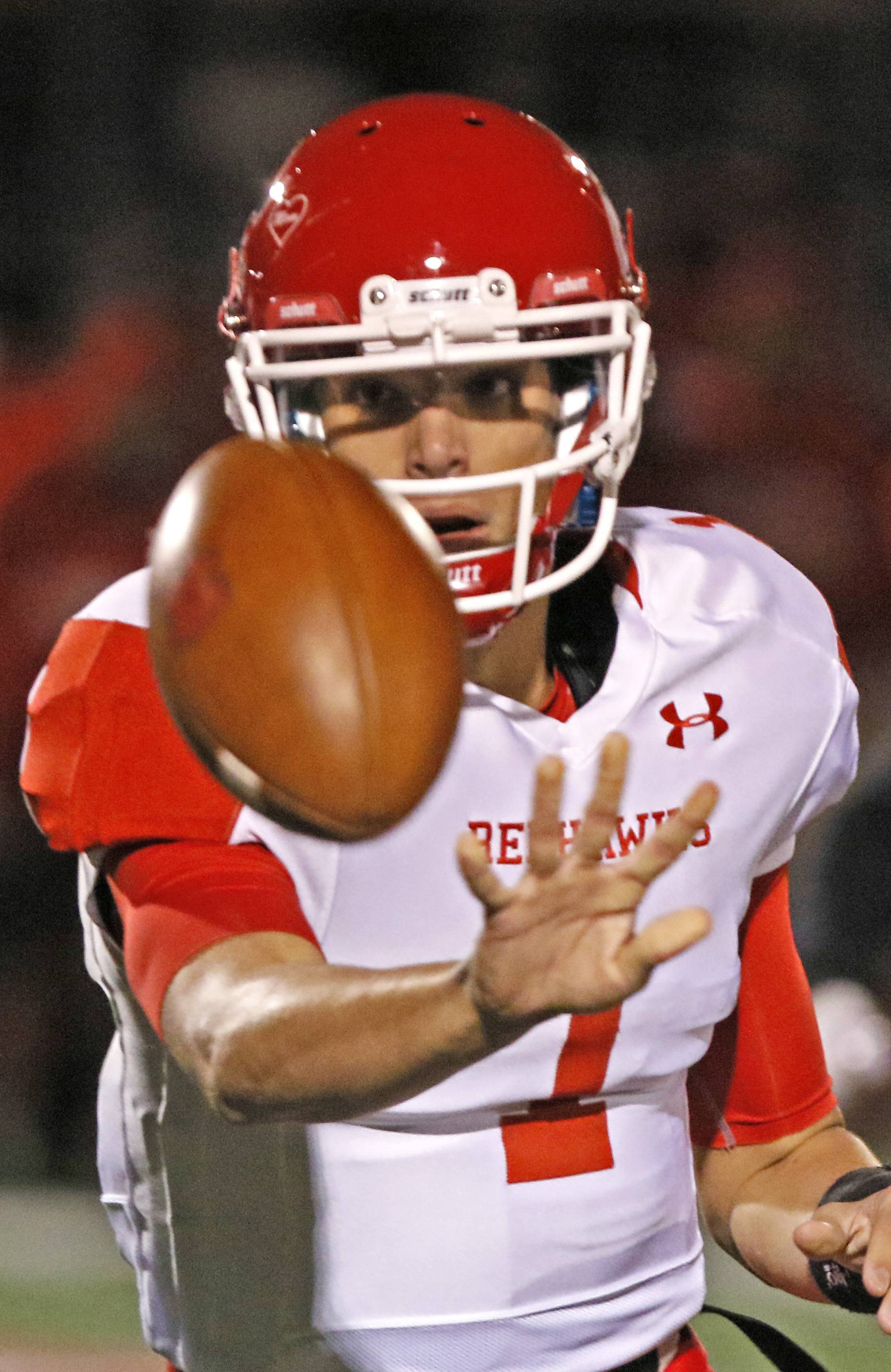 Naperville Central quarterback Payton Thorne pitches the football to a teammate against Homewood-Flossmoor during second round Class 8A football playoffs.