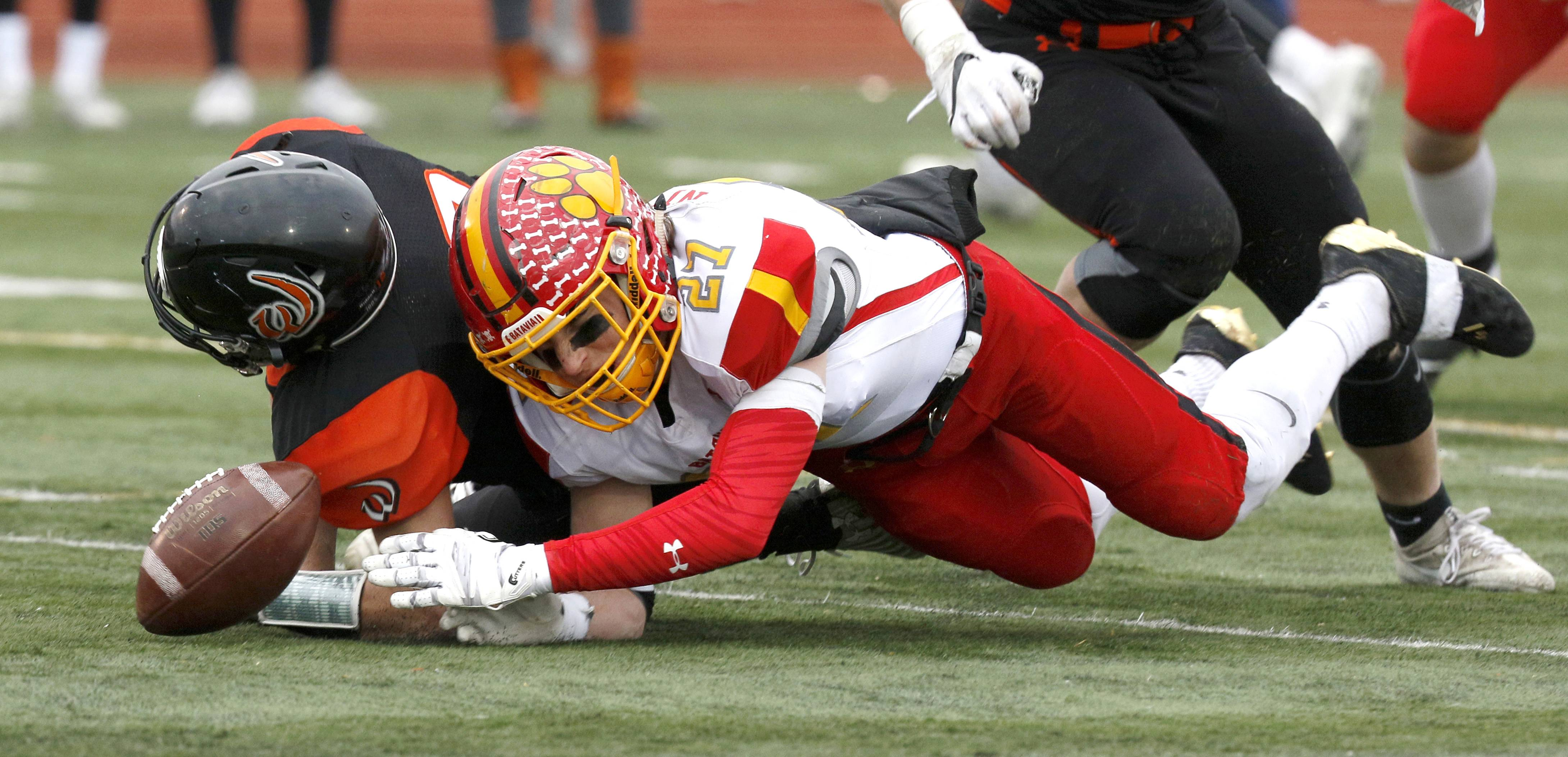 Batavia's Michael Niemiec (27) fights for a fumbled ball by Lincoln-Way West quarterback Anthony Senerchia during Class 7A football quarterfinal action in New Lenox.
