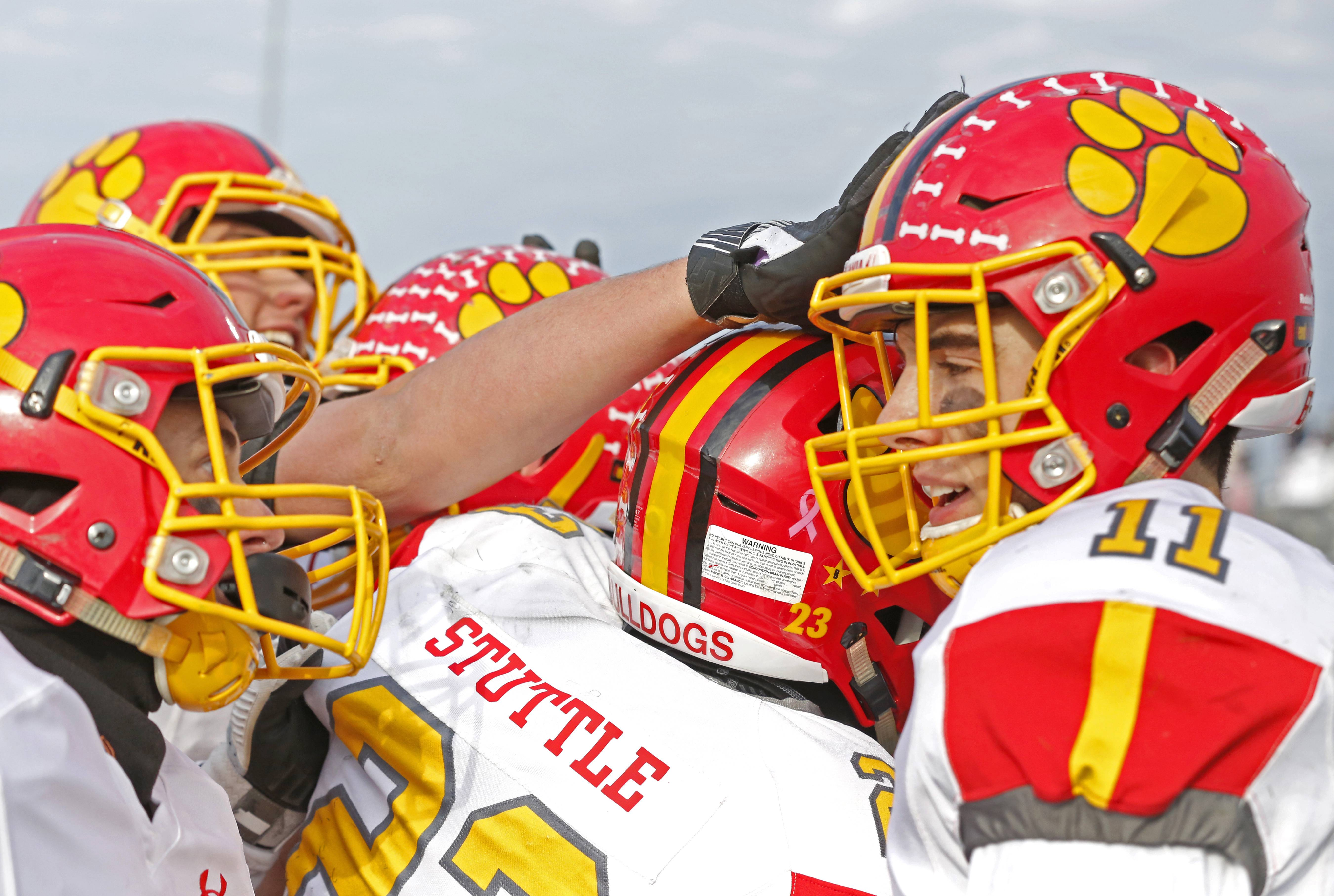 Batavia's Eric Peterson (11) is mobbed by teammates led by Tommy Stuttle (23) after scoring the first of his two touchdowns during a 20-10 win over Lincoln-Way West.