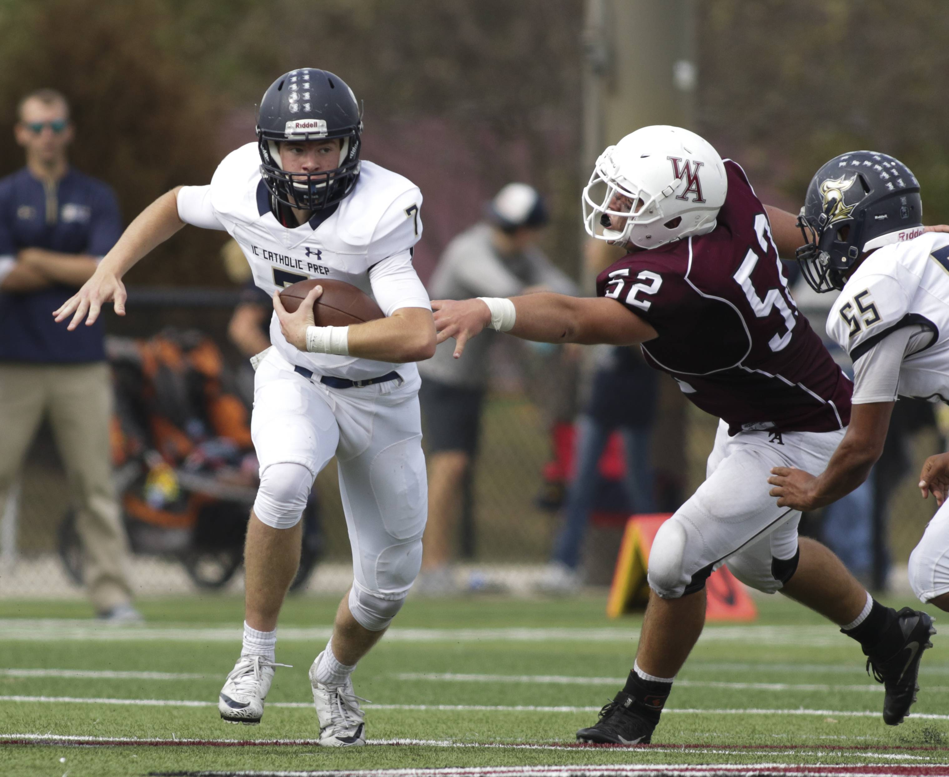 IC Catholic Prep quarterback CJ West, left, eludes the tackle of Derek Johanik of Wheaton Academy earlier this season.