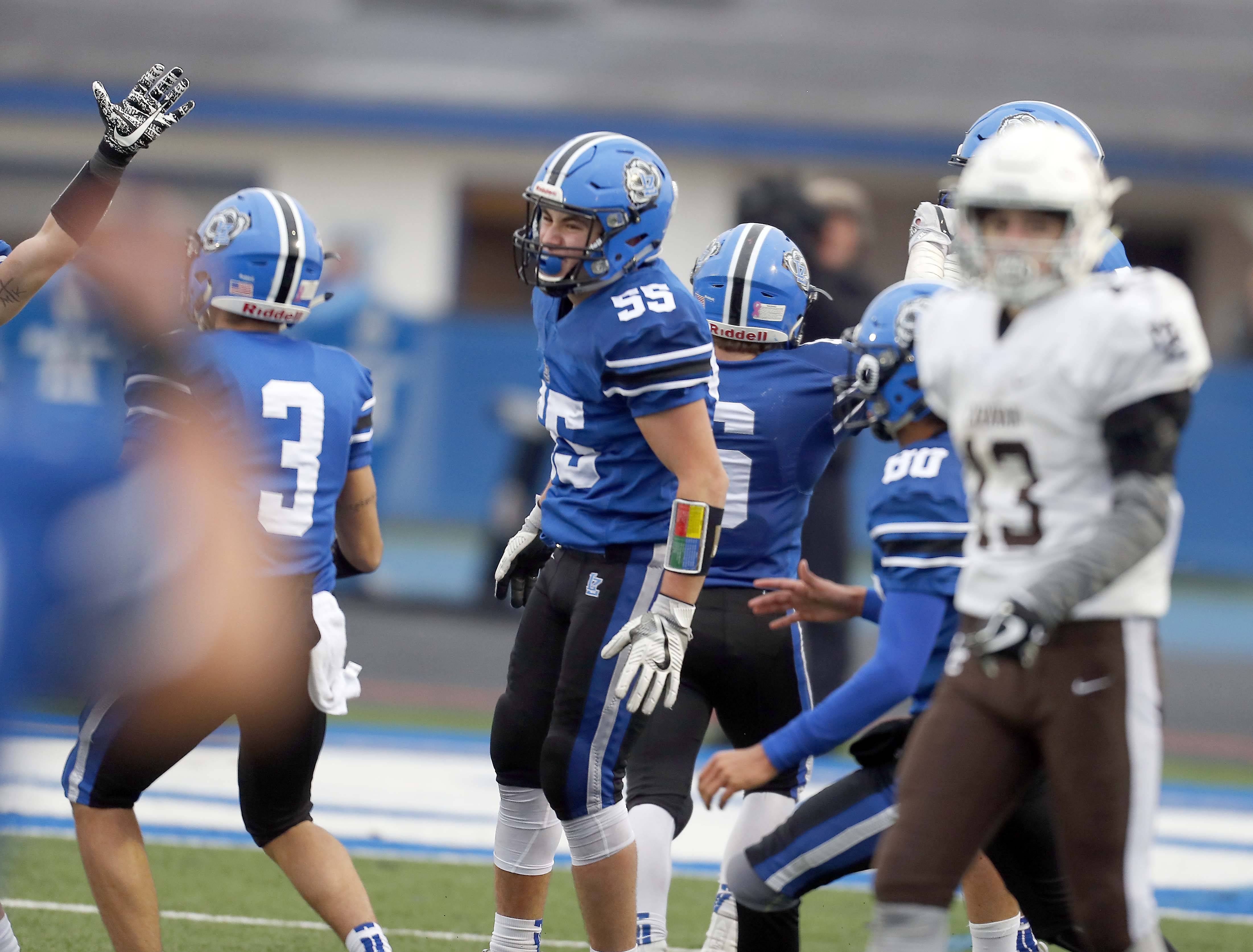 Lake Zurich's Bennett Amoroso (55) and his teammates celebrate a fourth-quarter interception Saturday during the Class 7A state semifinals against visiting Mt. Carmel.