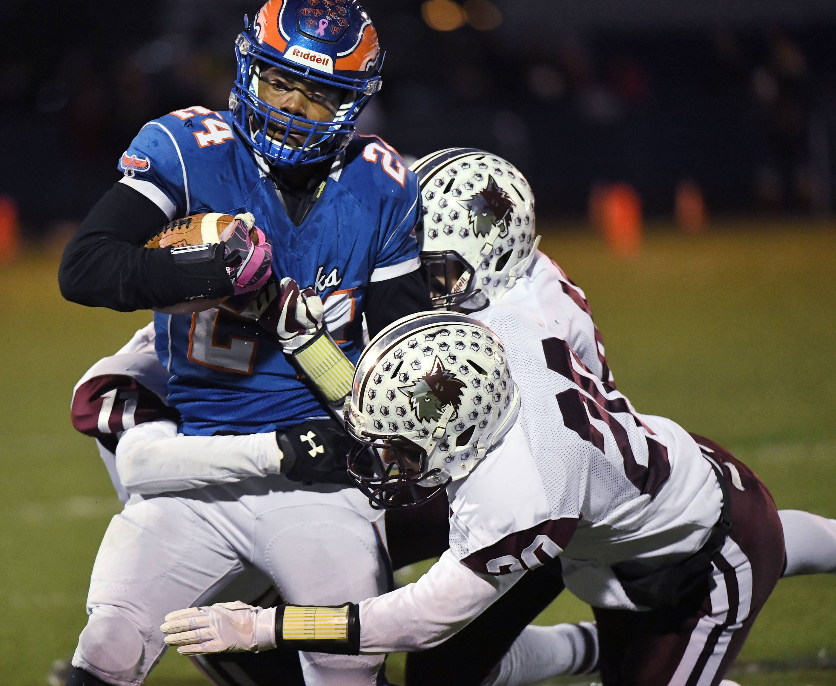 Hoffman Estates' Trevon Hall is brought down by Prairie Ridge's Justin Mikolajczewski, Sam Concialdi and Samson Evans on Saturday in the Class 6A state semifinals at Hoffman Estates.