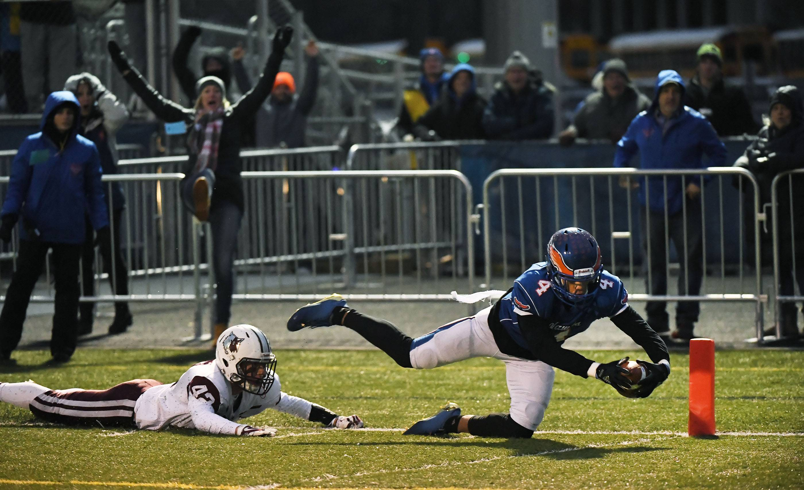 Hoffman Estates' Jayvon Blissett gets the ball over the goal line as his knee touches the turf while Prairie Ridge's Drew Fryer slides behind him in the first half of Saturday's Class 6A state semifinals at Hoffman Estates.