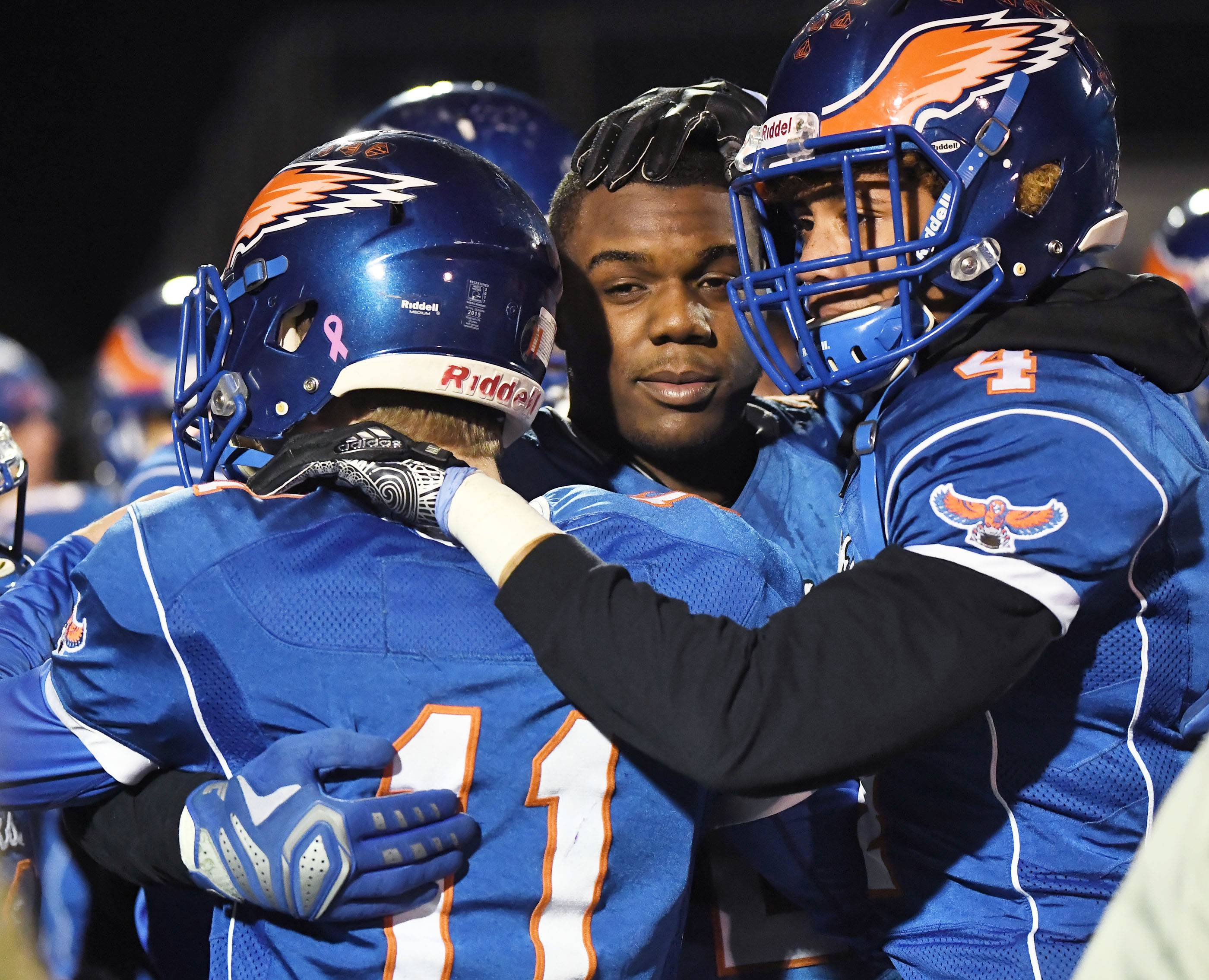 Hoffman Estates' Austin Coalson, Jaylan Alexander and Jayvon Blissett, right, hug it out after falling short against visiting Prairie Ridge on Saturday in the Class 6A state semifinals.