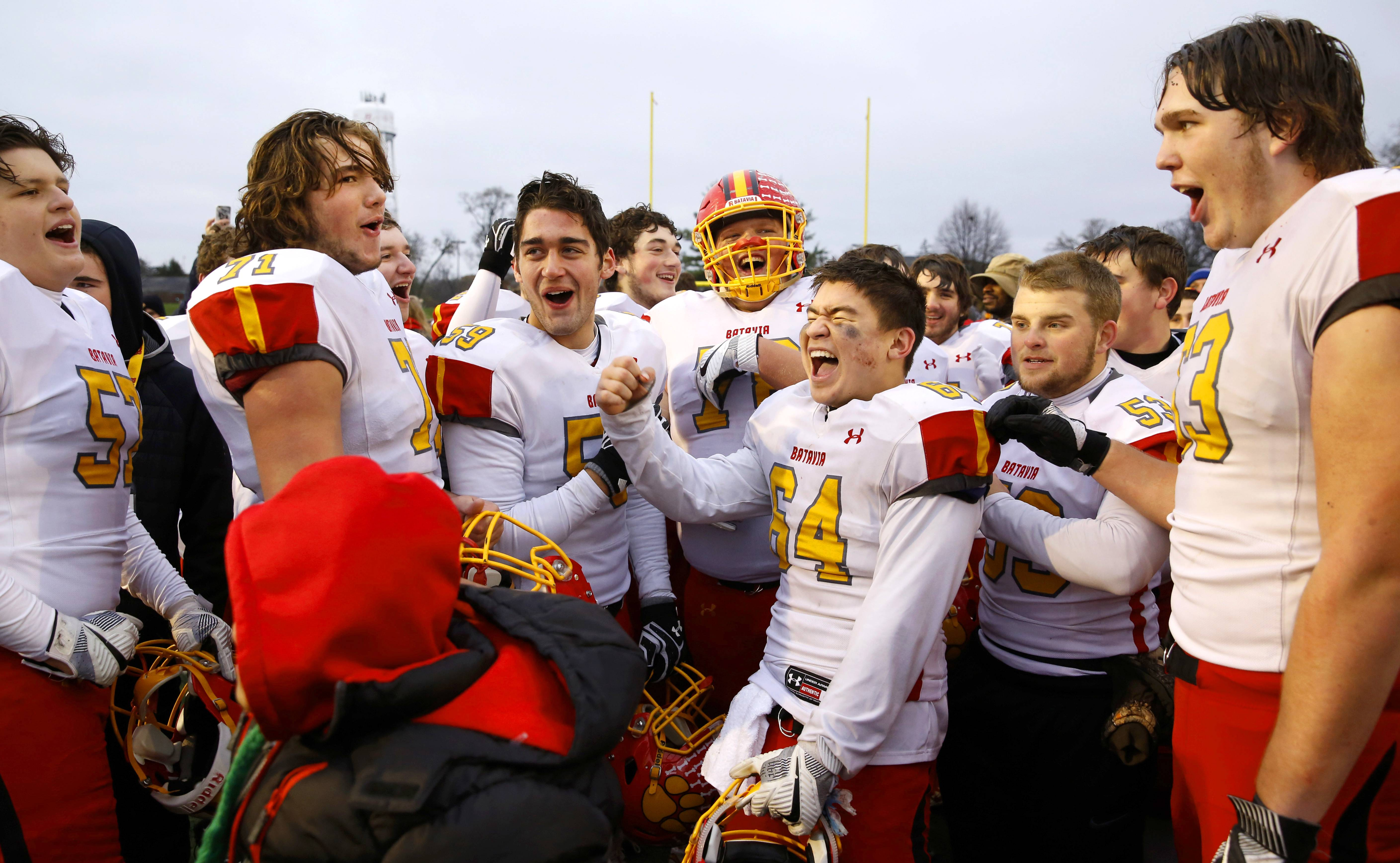 Batavia players, led by Benjamin Stoffels (64), celebrate after a 23-13 win over Benet Academy in the Class 7A football semifinals at Benedictine University in Lisle on Saturday.