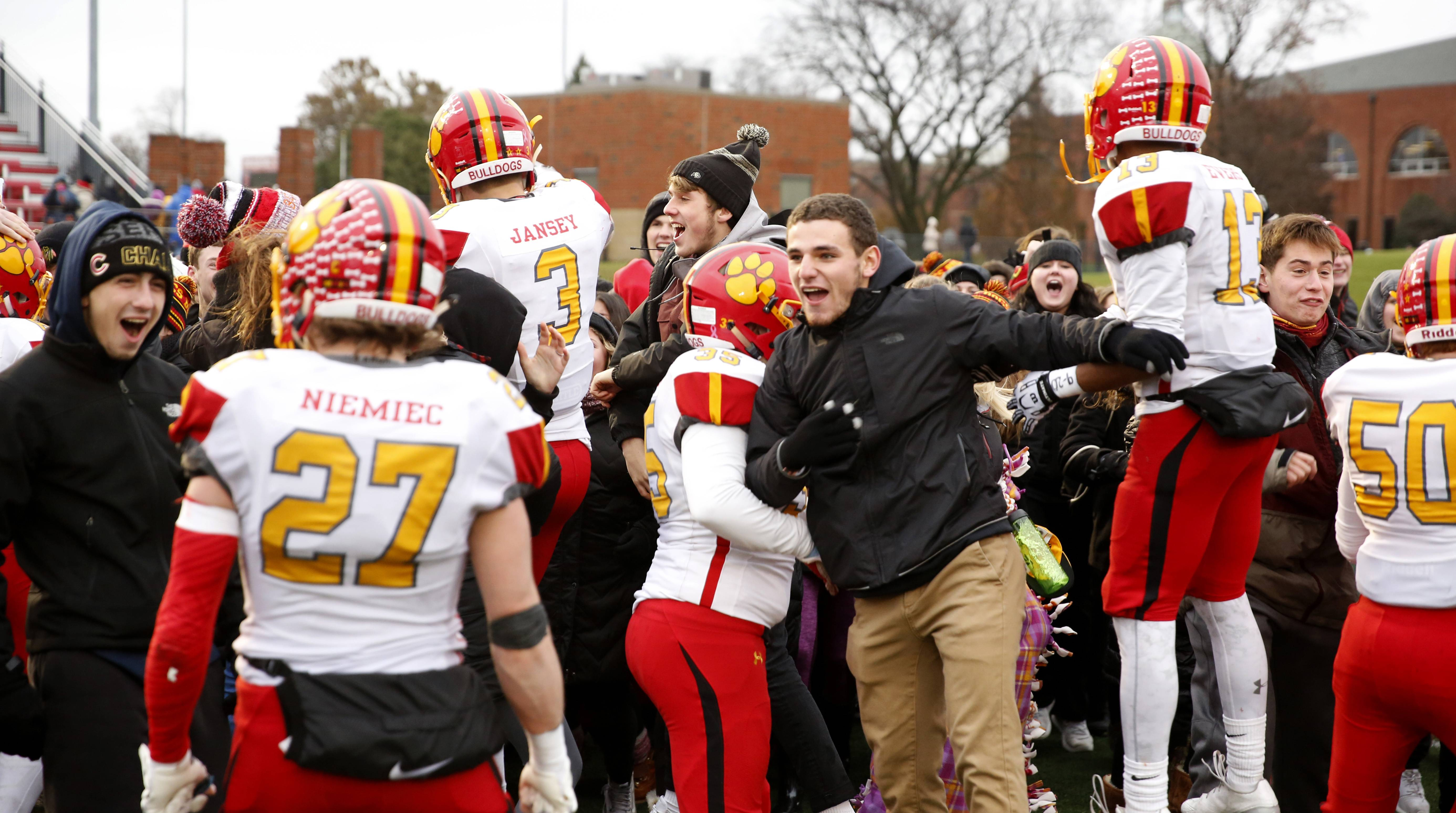 Batavia players and their fans celebrate a 23-13 win over Benet Academy in the Class 7A football semifinals in Lisle.