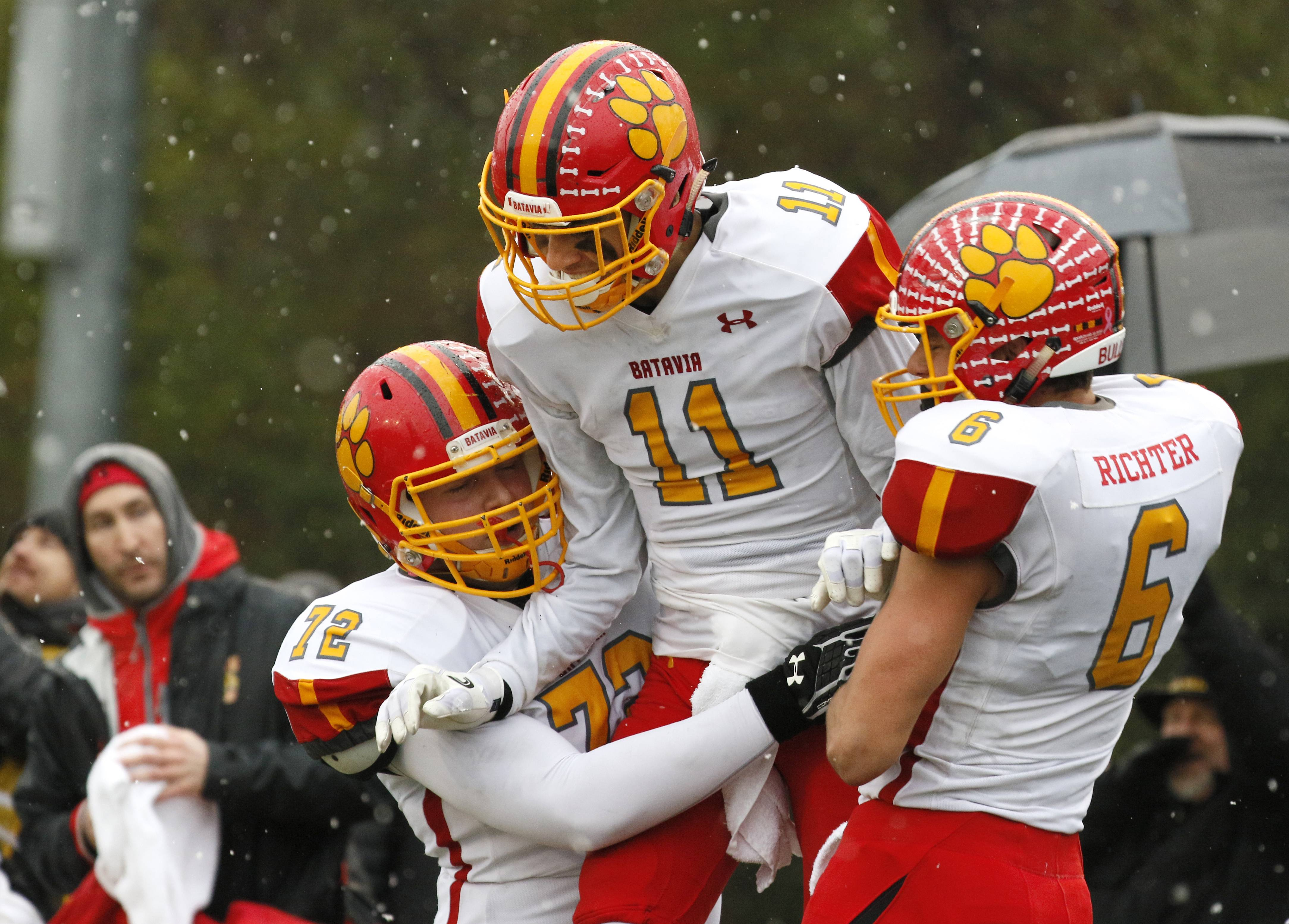 Batavia's Eric Peterson (11) is hoisted into the air by teammtaes Evan Holden (72) and Collin Richter (6) after scoring his second touchdown in the Bulldogs' 23-13 win over Benet Academy in the Class 7A semifinals at Benedictine University in Lisle.