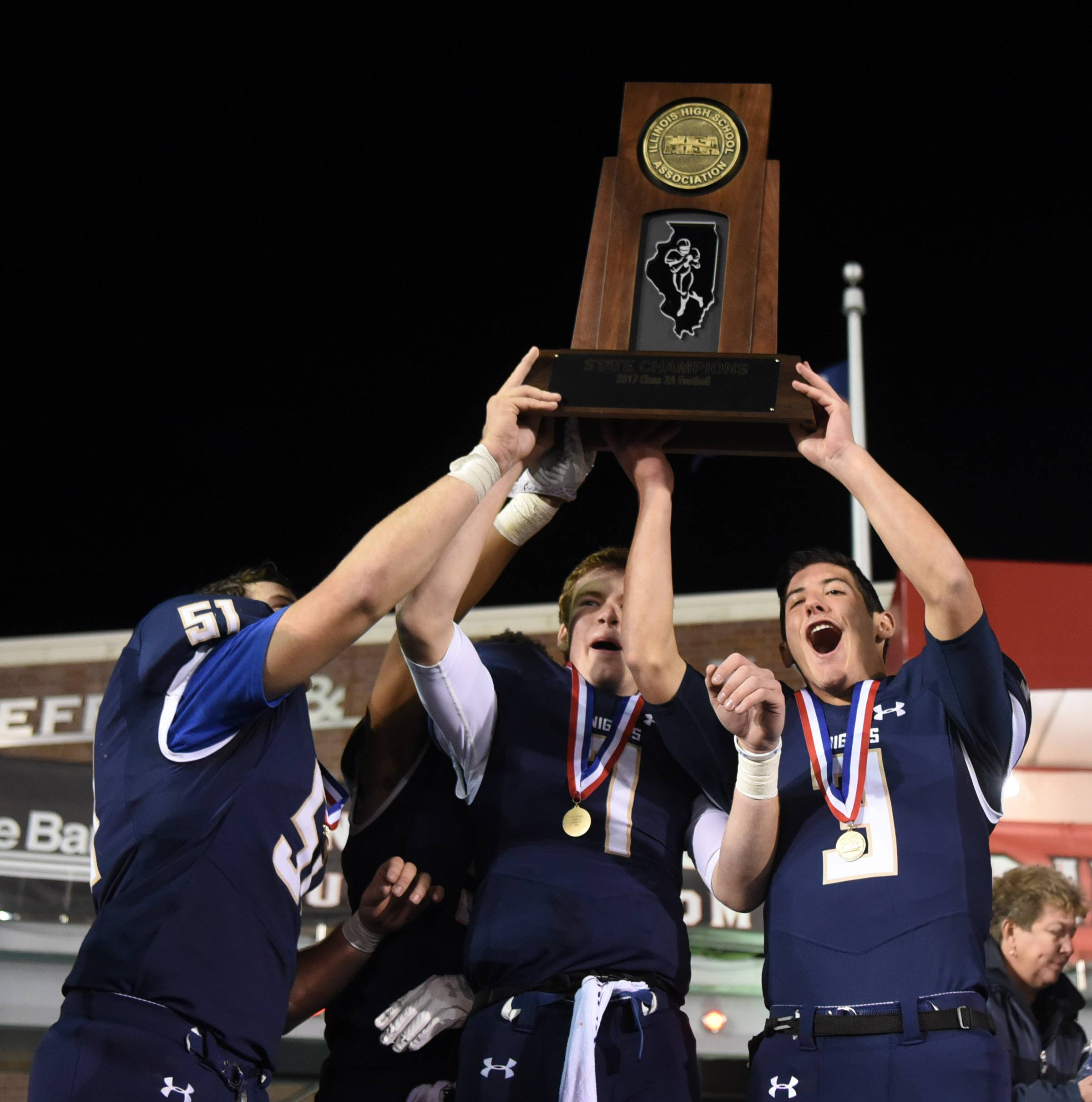 The State Championship trophy is raised by, from left, IC Catholic's Dylan Packer, Khalil Saunders, CJ West and Luke Ricobene at the conclusion of the Class 3A championship came at NIU's Huskie Stadium in DeKalb Friday. IC Catholic defeated Pleasant Plains 35-0.