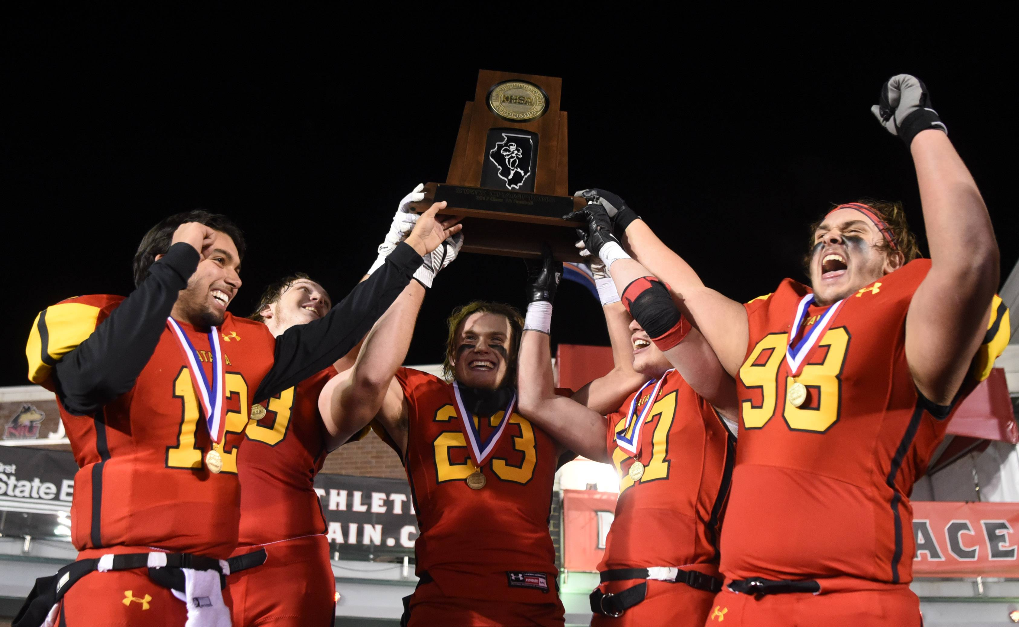 Left to right, Batavia's Riley Cooper, Nolan Eike, Tommy Stuttle, Michael Niemiec and Maxwell McFadden hold their first-place trophy following their 21-14 OT win over Lake Zurich during the Class 7A championship game at Huskie Stadium in DeKalb Saturday.