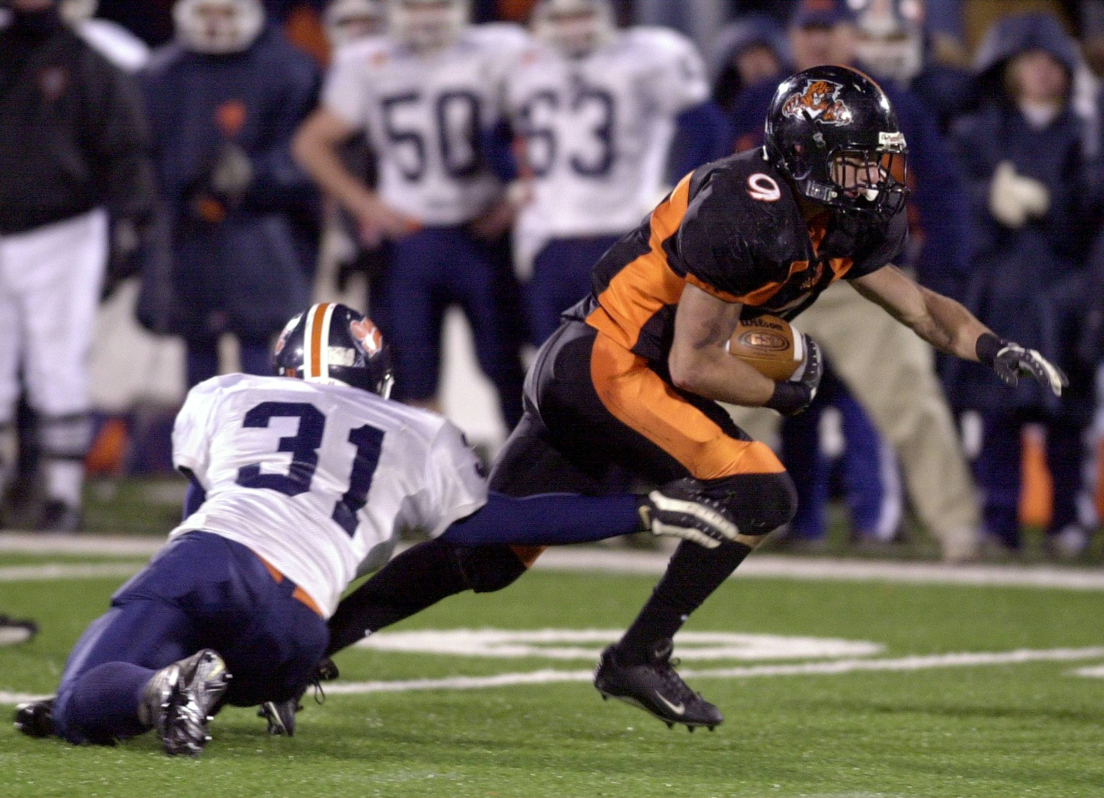 Libertyville's Santino Panico eludes Oswego's Adrian Pyneburg for a long gain in the fourth quarter of the Wildcats' 28-21 loss in double overtime in the 2003 Class 7A state title game.