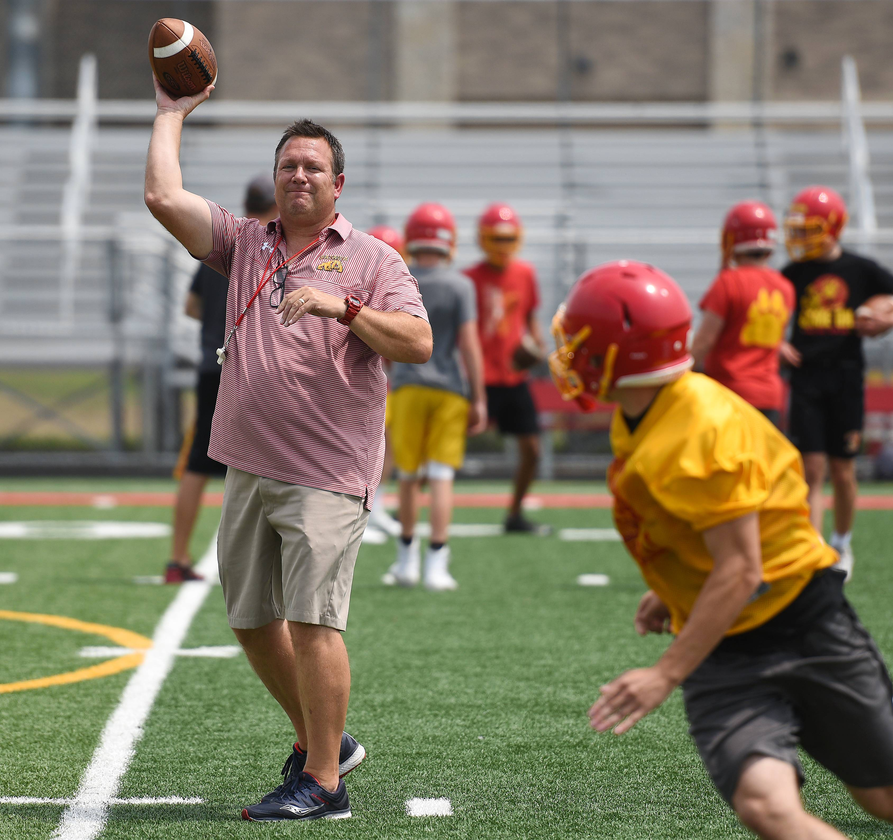 Batavia head coach Dennis Piron throws passes to his players during the first day of football practice at Batavia High School Monday. The Bulldogs are defending state champions.