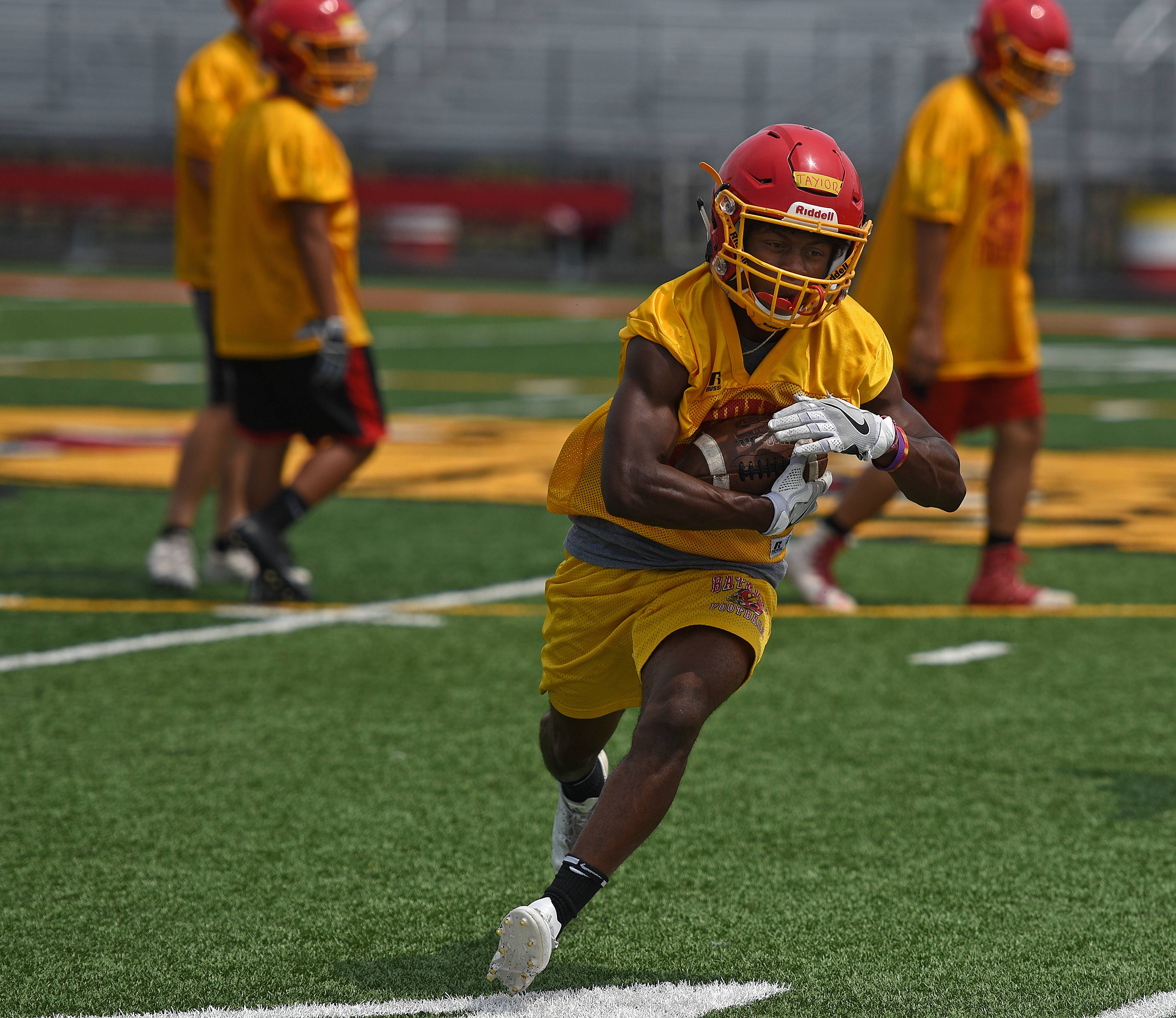 Running back Art Taylor cuts to the outside during the first day of football practice at Batavia High School Monday.