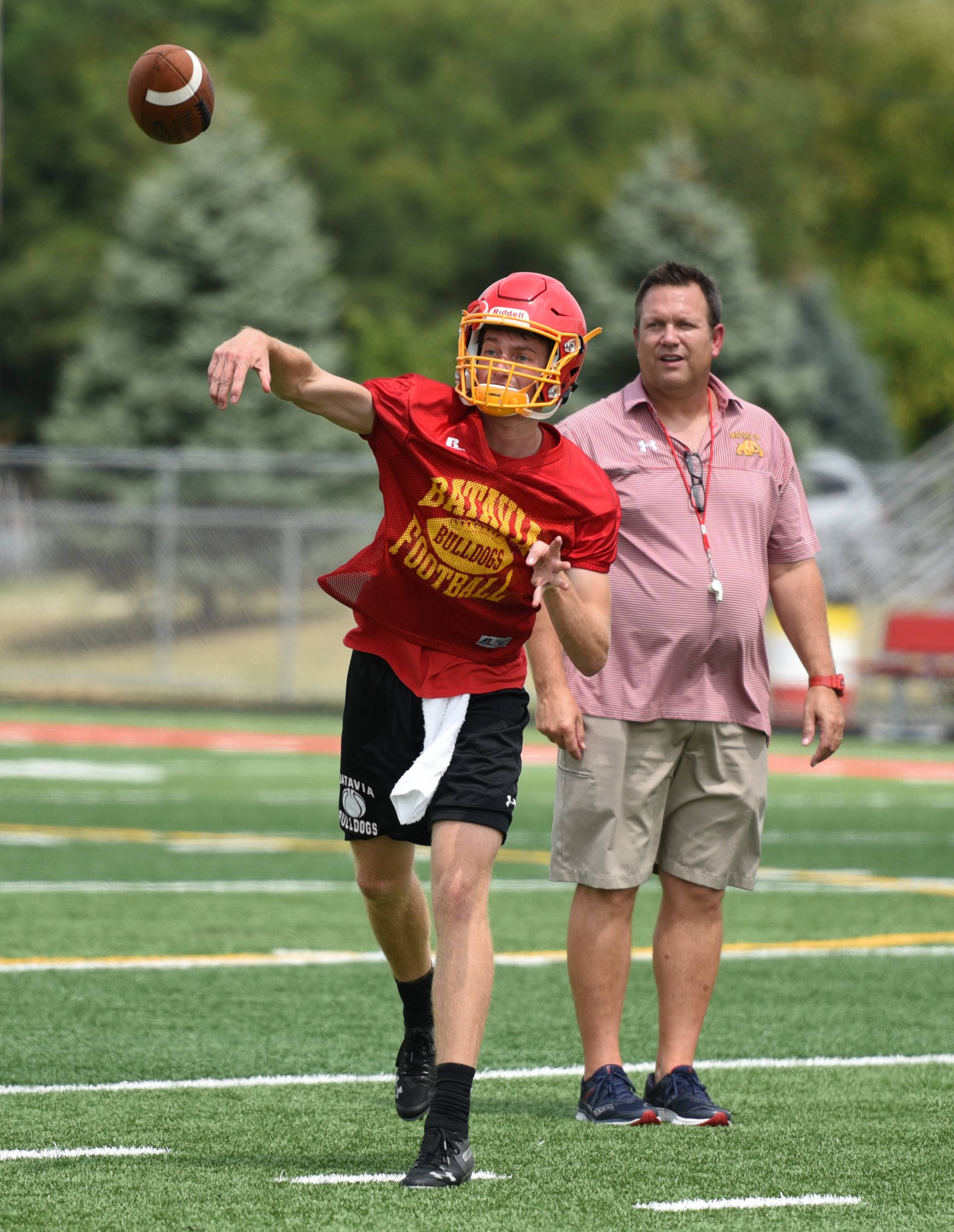 Quarterback Jack Meyers works with coach Dennis Piron during the first day of football practice at Batavia High School Monday.