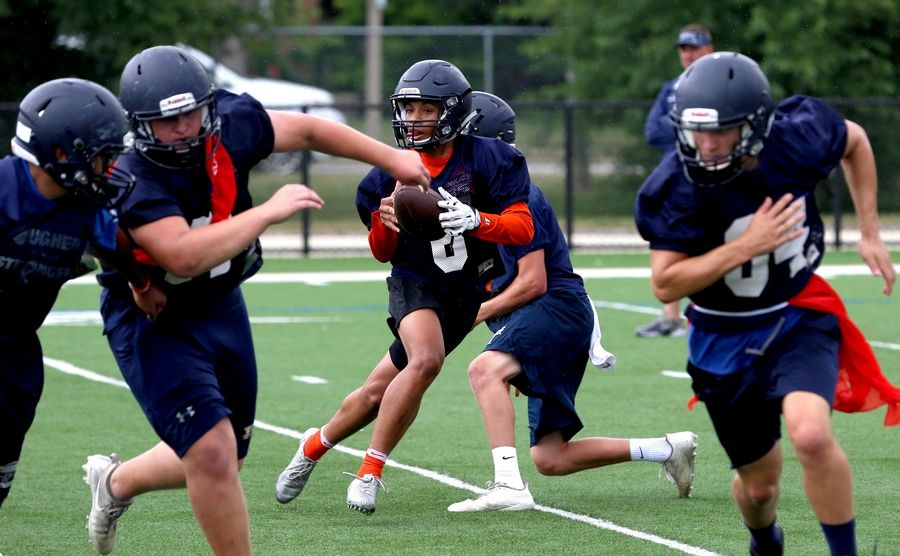 The Knights of IC Catholic Prep practiced on Monday at Lewis Stadium on the Plunkett Athletic Complex in Elmhurst. Here, Camarion Hood, center, looks for an option after receiving a handoff.