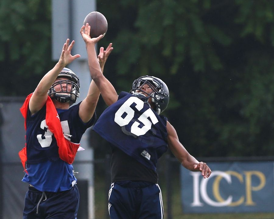 The Knights of IC Catholic Prep practiced on Monday at Lewis Stadium on the Plunkett Athletic Complex in Elmhurst. Jake Lytton, left, and Jalen Bates vie for a pass.