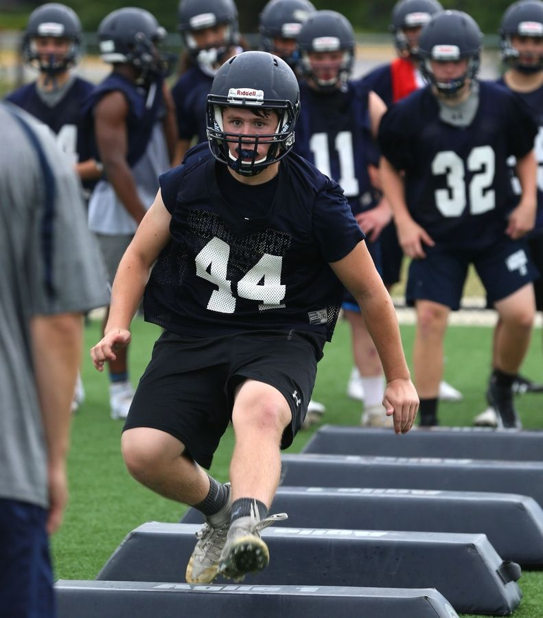 The Knights of IC Catholic Prep practiced on Monday at Lewis Stadium on the Plunkett Athletic Complex in Elmhurst. Kevin Cooke completes a drill.