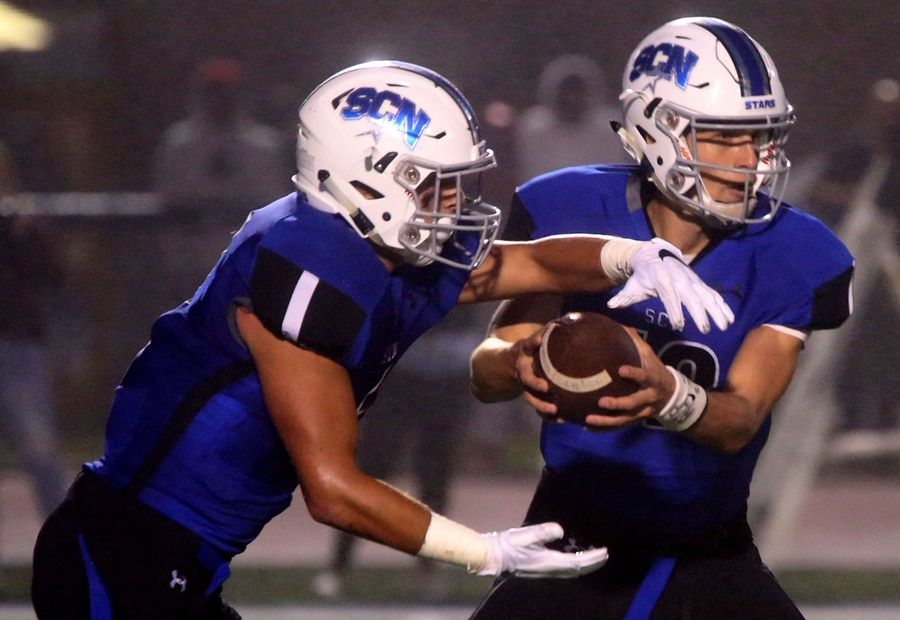 St. Charles North's quarterback Peyton Brown, right, hands off to Sam DeMarco against Schaumburg during the North Stars' victory Friday night in St. Charles.
