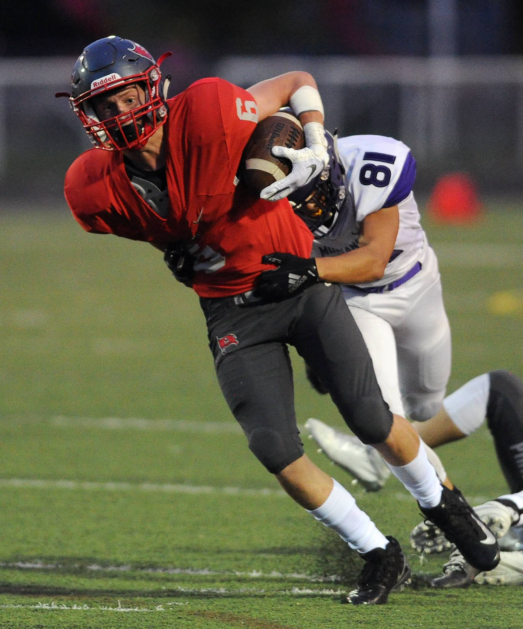 Palatine's Jake Gronwick runs for yardage and is stopped by Rolling Meadows' TJ Williams in the first quarter Friday.