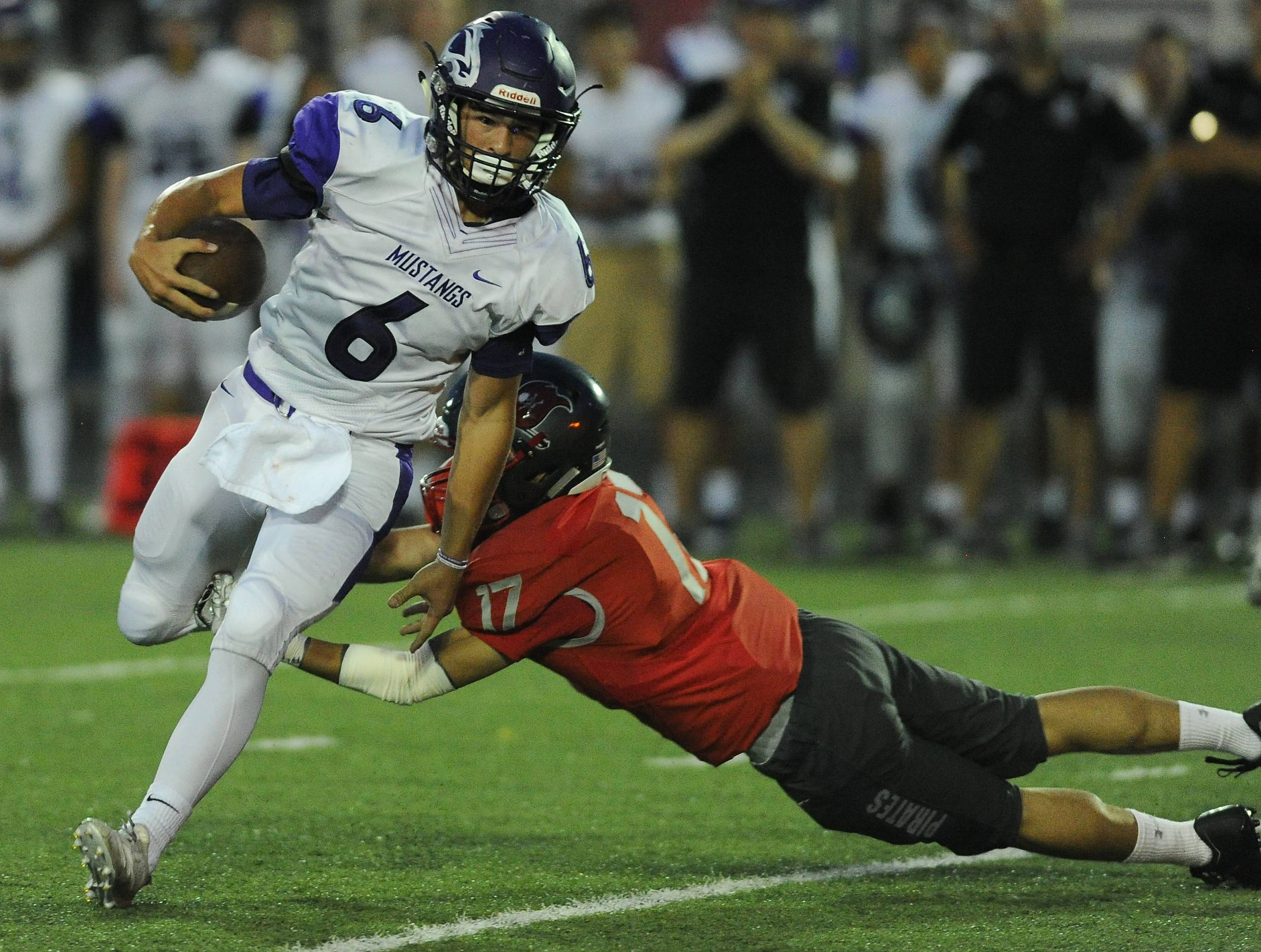 Rolling Meadows' Jordan Wiles picks up a first down by slipping past Palatine defenders in the first quarter of the Mustangs' 56-28 victory last week. Rolling Meadows has a Week 3 matchup with Highland Park at 7:30 p.m. Friday.