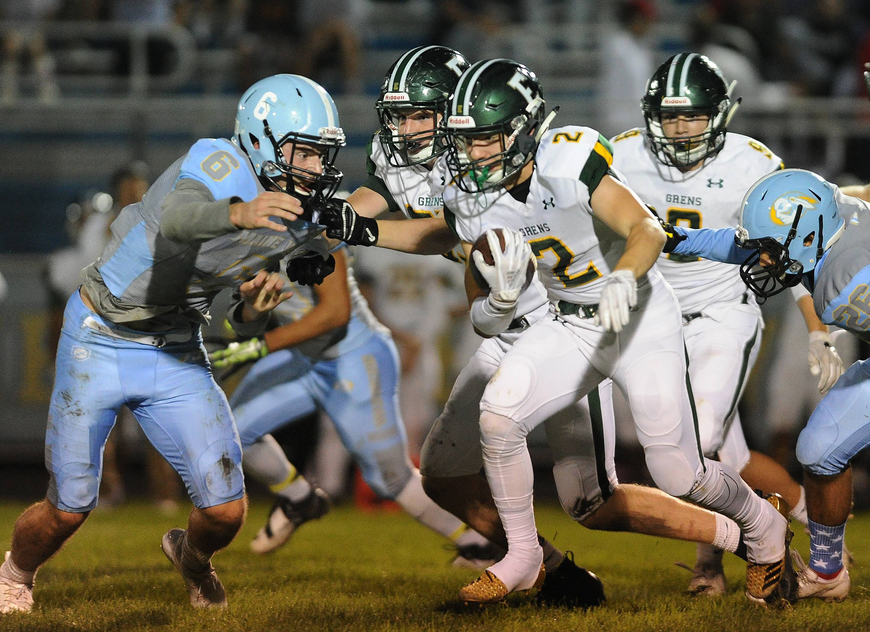 Elk Grove's Ian Ridge adds a 30-yard punt return in the second quarter to his highlight reel as Maine West's Ely Grimmer closes the gap in the varsity matchup at Maine West on Friday.