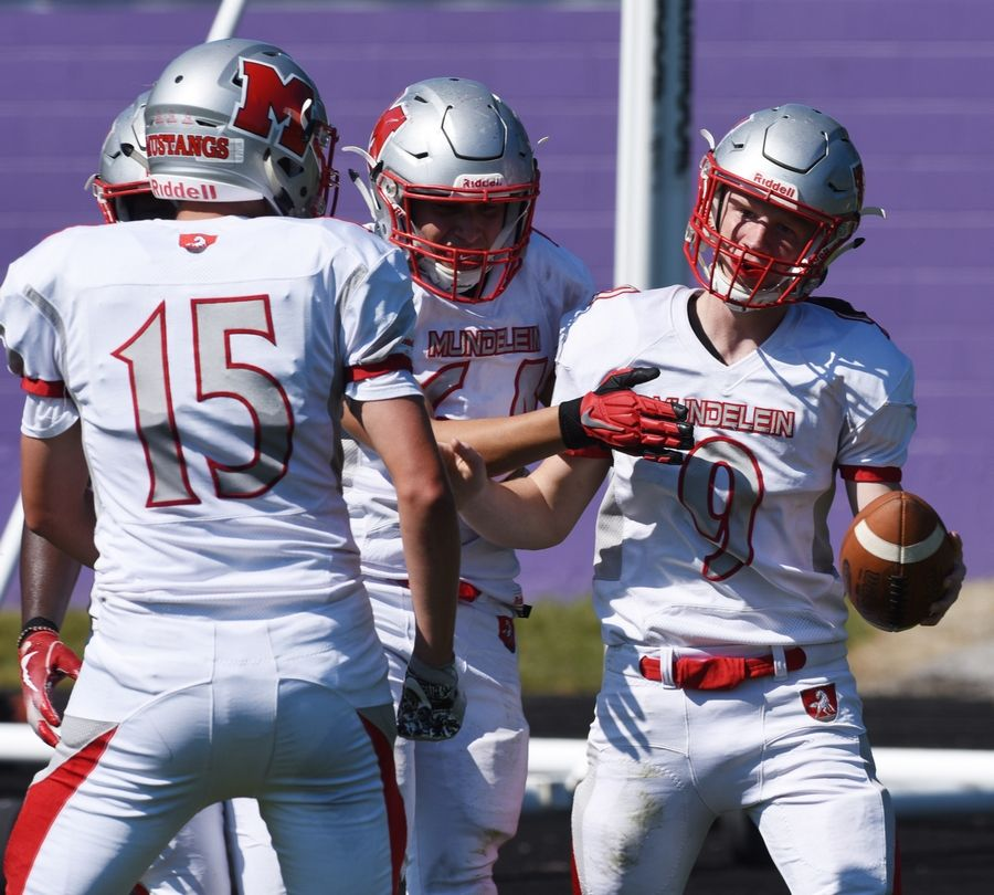 Mundelein's Isaac Wellman, right, celebrates a touchdown with teammates Brandon Paluch, left, and Alex Hurtado during Saturday's game at Weiss Field in Waukegan.