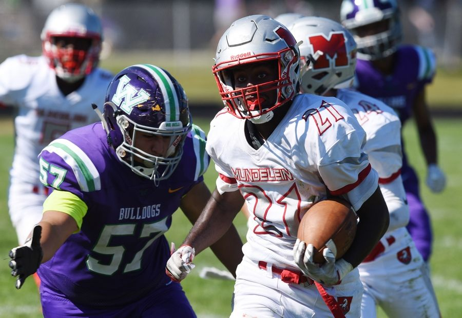 With Waukegan's Rodrigo Salgado-Chino in pursuit, Mundelein's Tabor Alemu carries the ball just short of the goal line following a fumble recovery during Saturday's game at Weiss Field in Waukegan.