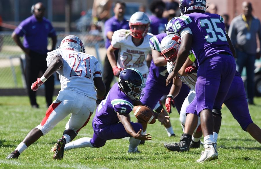 Mundelein's Tabor Alemu (21) closes in on a Waukegan fumble, which he took just short of the goal line during Saturday's game at Weiss Field in Waukegan. The Mustangs scored on the next play.