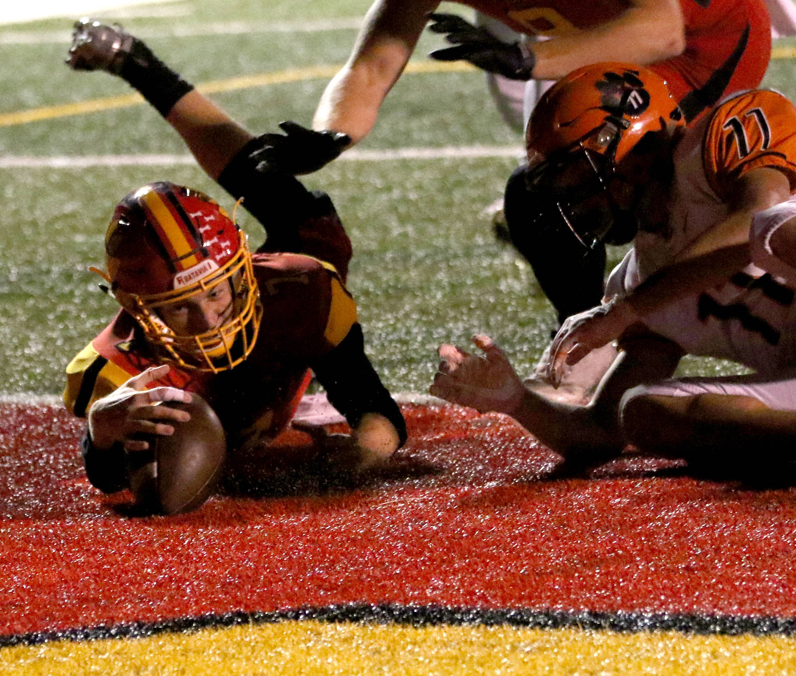 The ball popped loose from the hands of Batavia's Jack Meyers in the first quarter in the end zone against Wheaton Warrenville South during varsity football at Bulldog Stadium in Batavia Friday night. Here, Meyers recovers the ball for a touchdown.
