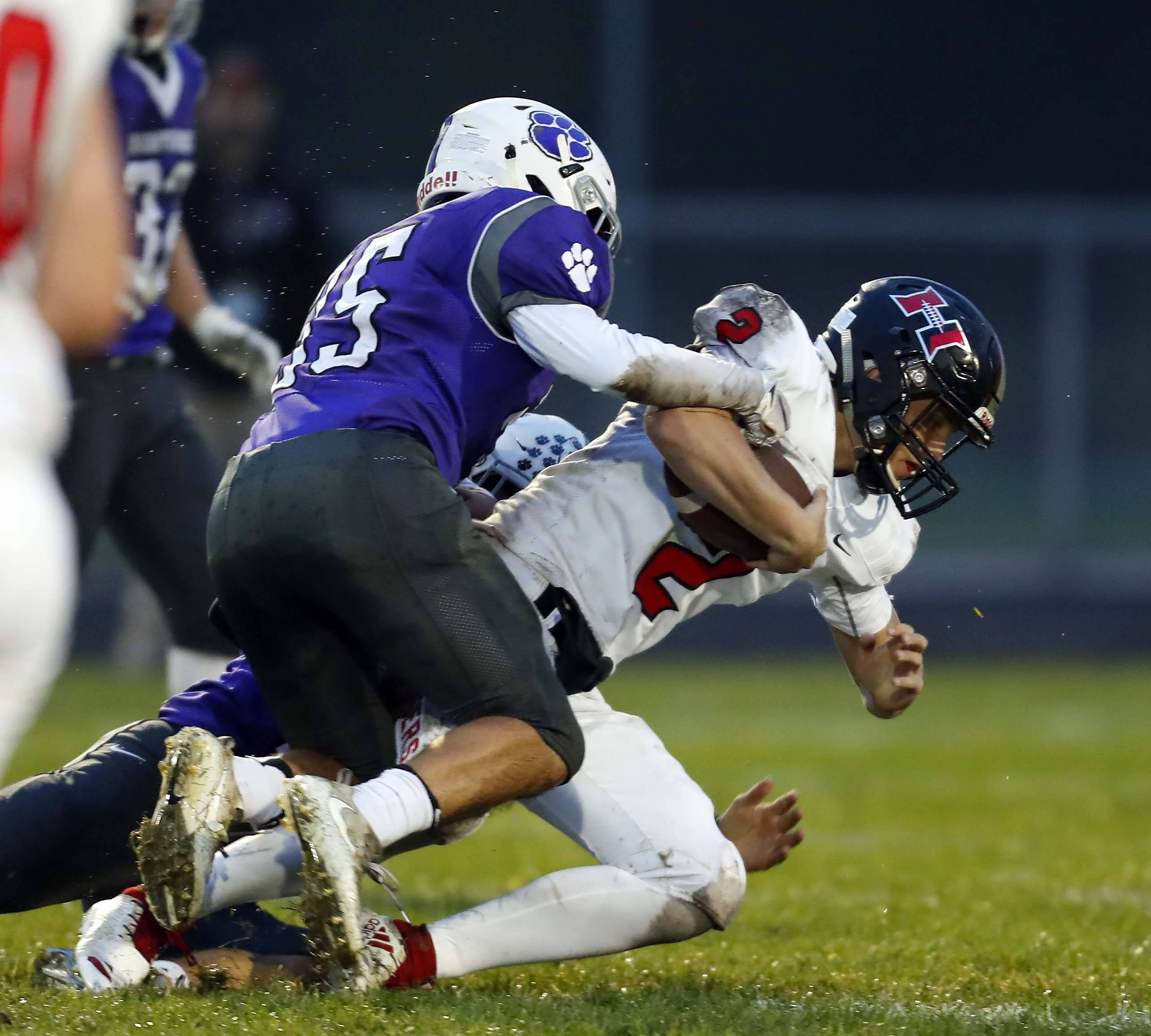 Hampshire's William Negron (35) helps bring down Huntley's Christopher Raffin (2) Friday during football in Hampshire.