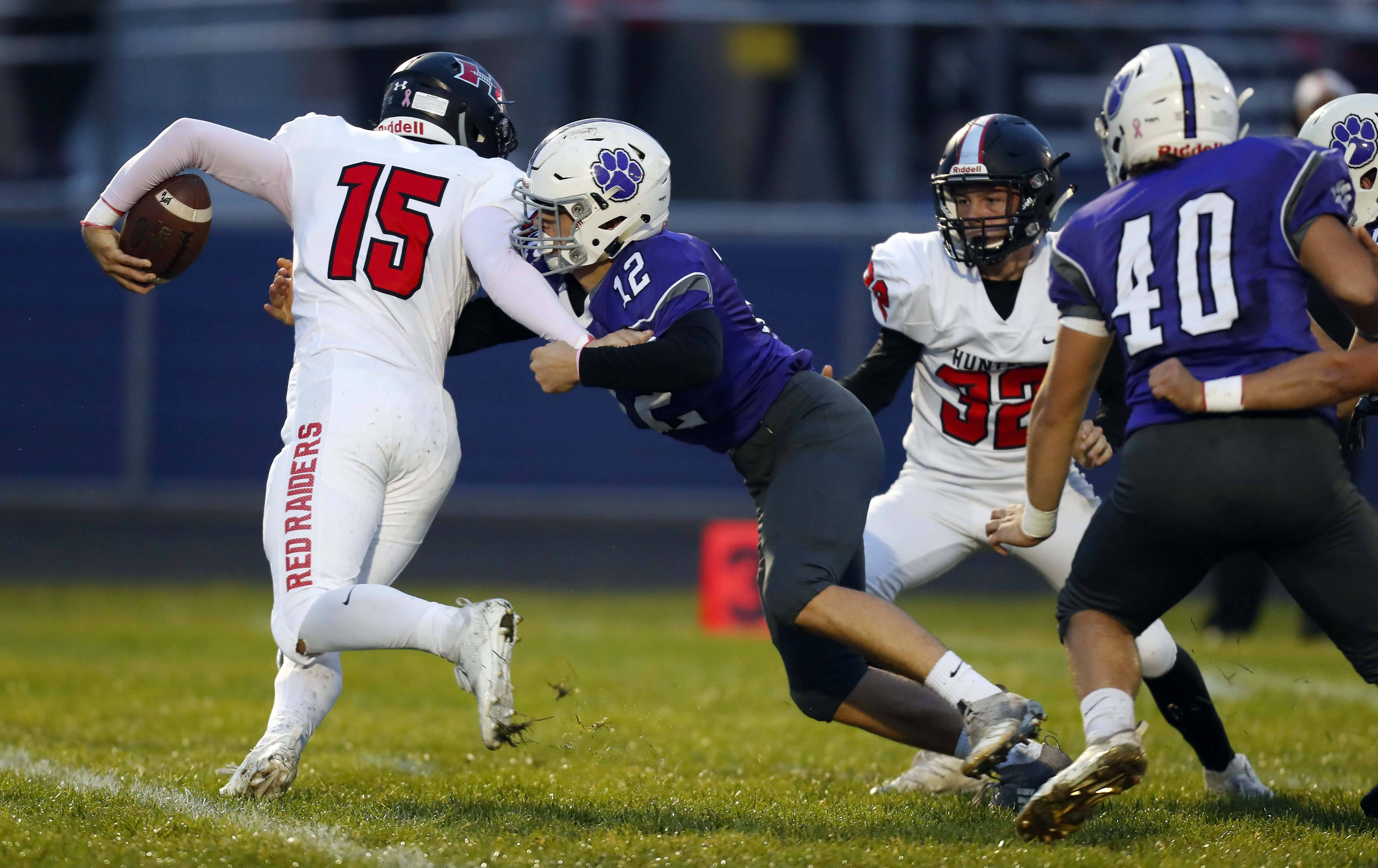 Hampshire's John Brady Young (12) pressures Huntley's Michael Boland (15) Friday during football in Hampshire.