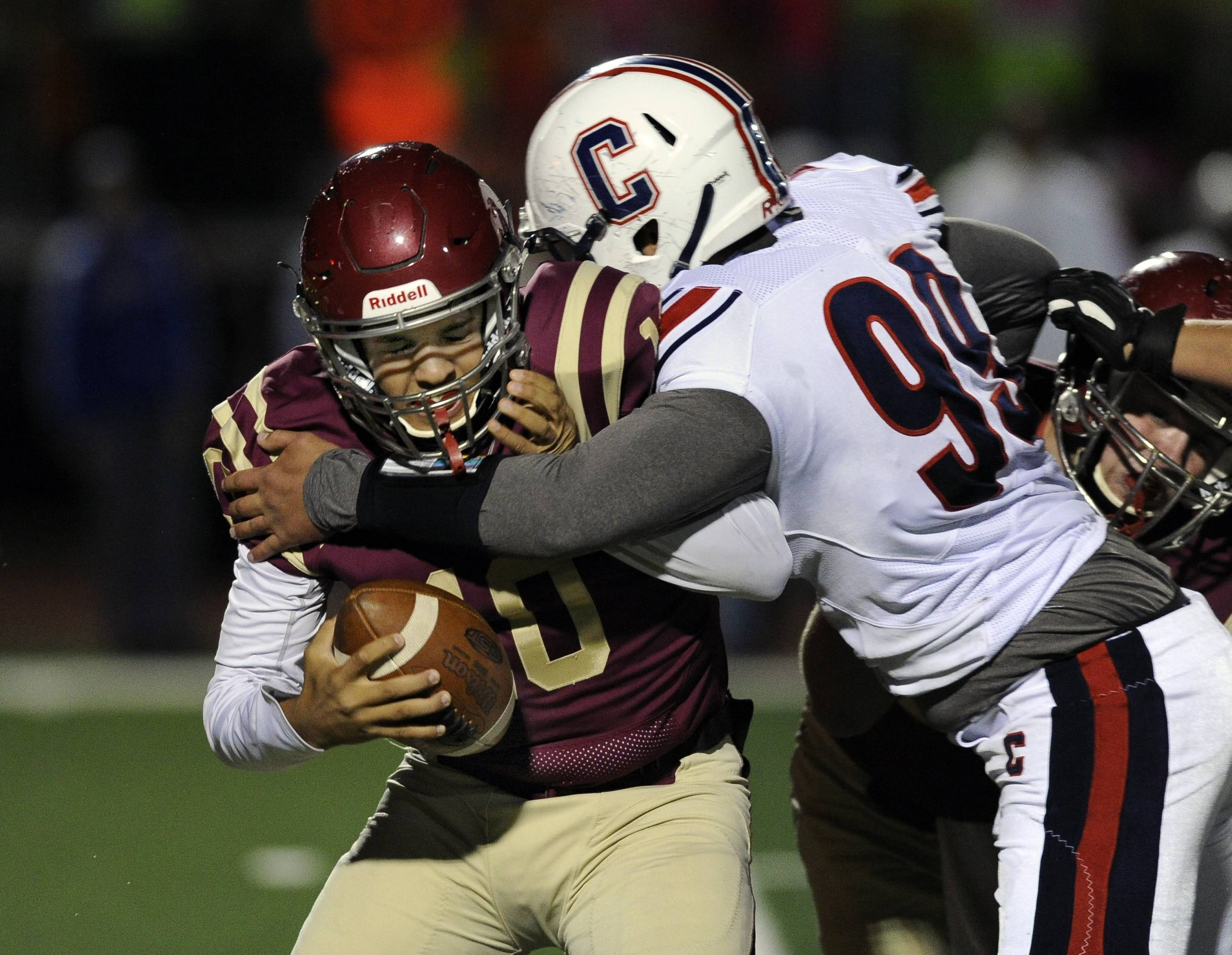 Schaumburg quarterback Marcus Ross is sacked by Conant's Frank Daidone earlier this season. Schaumburg takes on Barrington Friday night while Conant hosts Palatine.
