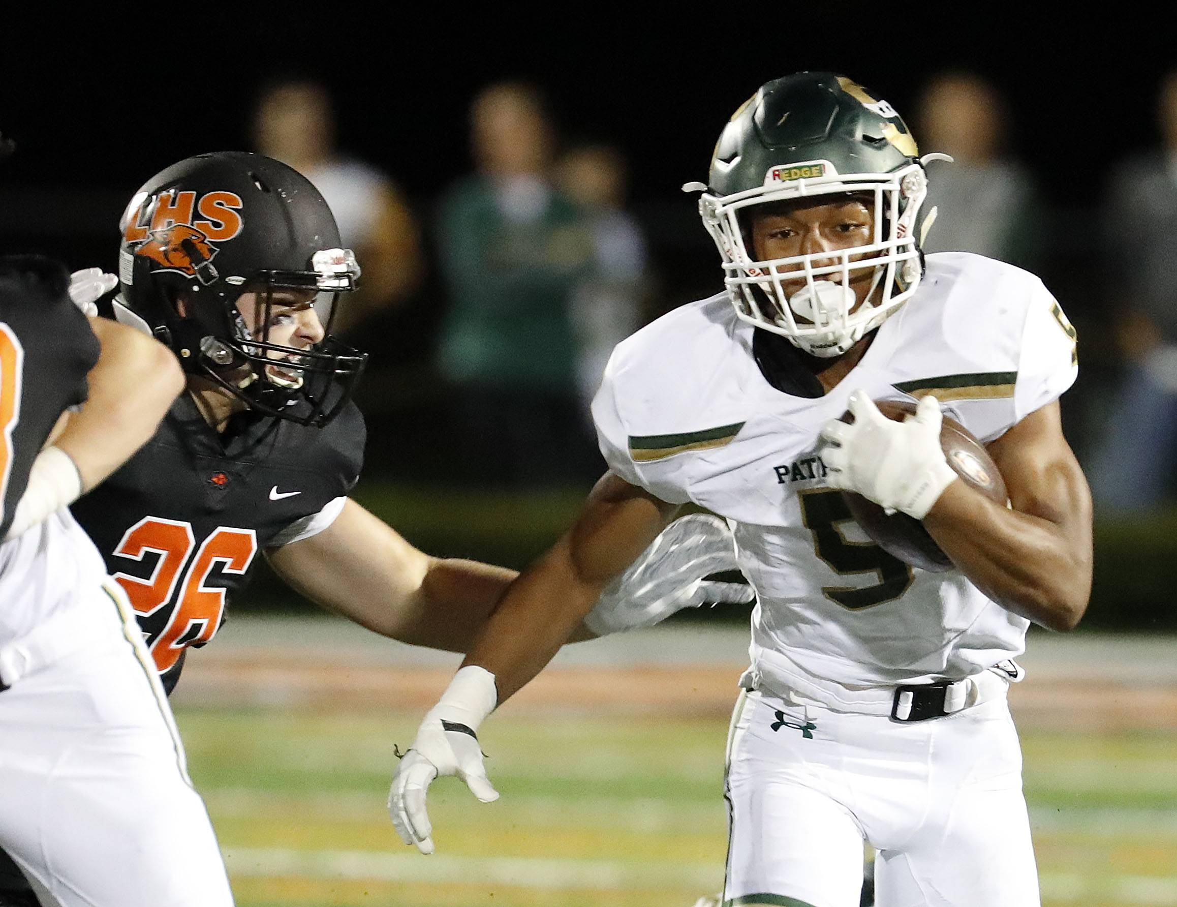Stevenson's JeanMarc Etienne gets around Libertyville's Chase Quigley earlier this season. The Patriots take on Warren Friday night with the North Suburban Conference title on the line.