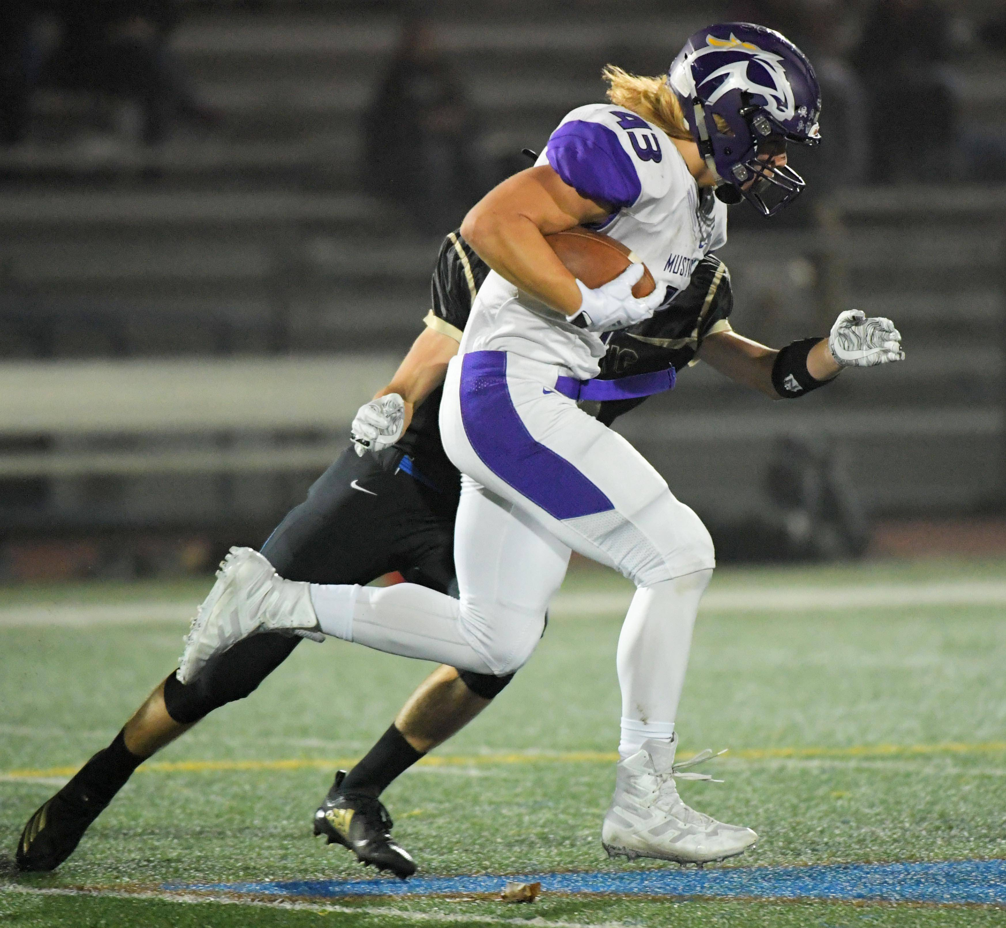 Rolling Meadows' Tim Szylak gets past Wheeling's Danny Provost earlier this season. Szylak, the Northwest suburbs' leading rusher, and the Mustangs will host Hersey in an MSL East showdown Friday.