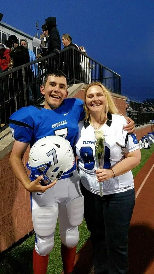 Vernon Hills senior Anthony Berktold, left, with his mom Heidi at last Friday's game against Maine East. Anthony, a special needs student, was allowed to suit up and even scored a touchdown in the Cougars' 57-6 win.