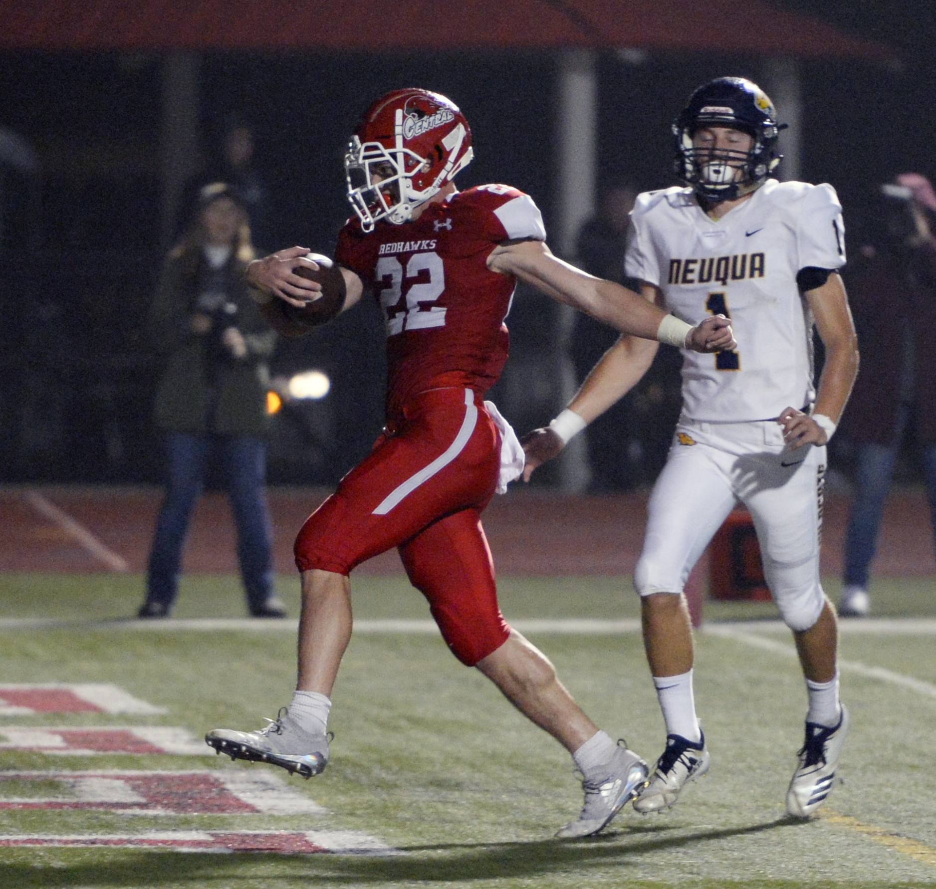 Naperville Central's Danny Hughes struts into the end zone for a second-quarter touchdown, running by Neuqua Valley's Patrick Hoffmann during the varsity football matchup in Naperville on Friday.